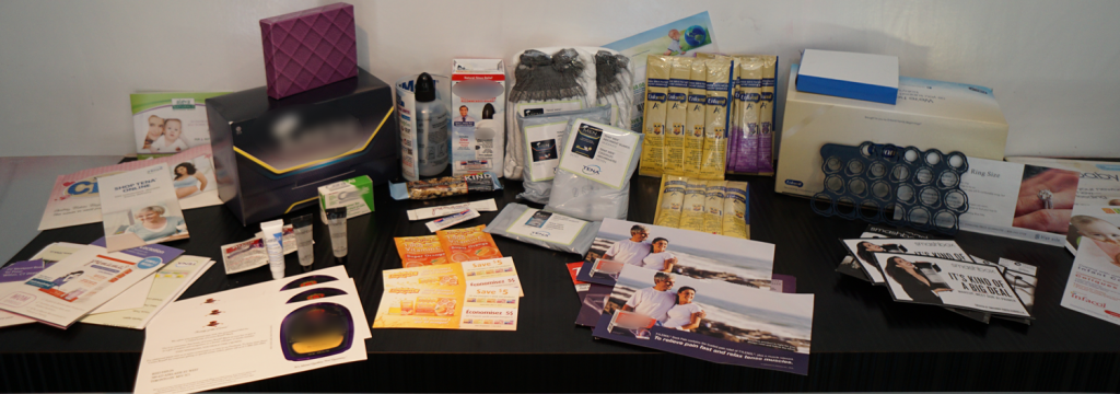 A huge collection of free product samples and inserts on a table.