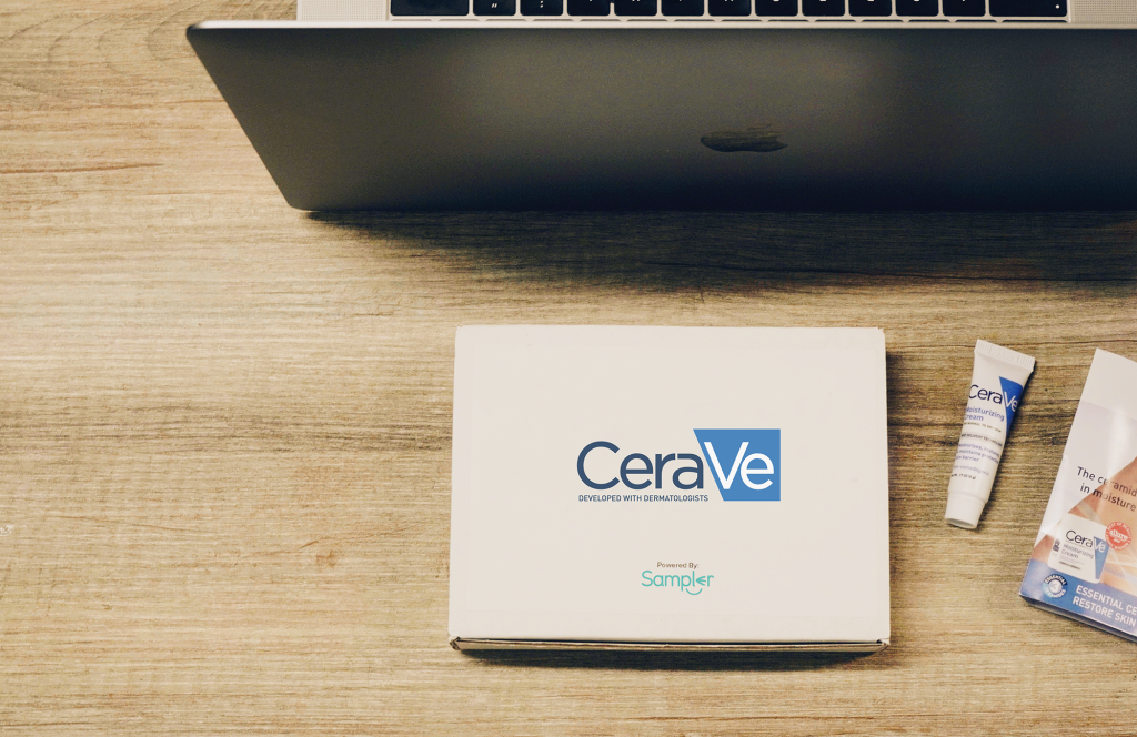 A CeraVe and Sampler box with CeraVe products to the right and a labtop in front.