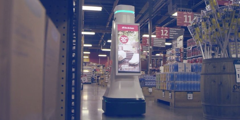 A robot with a sale offer on the front moving down the aisles of a department store.