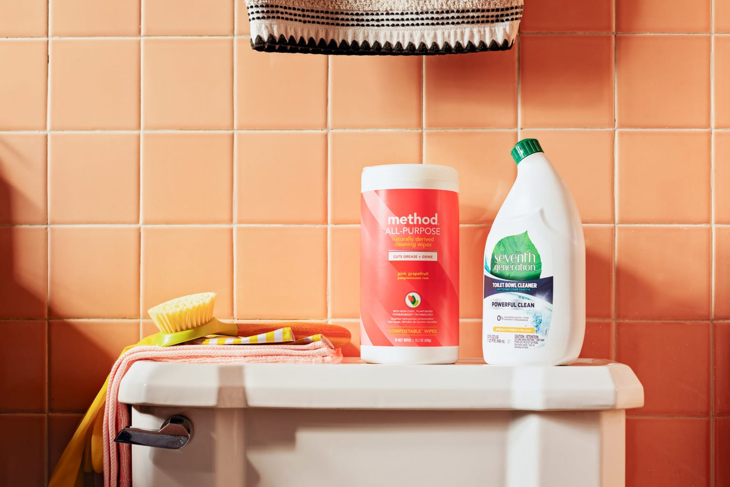 A  method® pink grapefruit cleaning wipes sample on top of a  toilet with other bathroom cleaning products and tools.