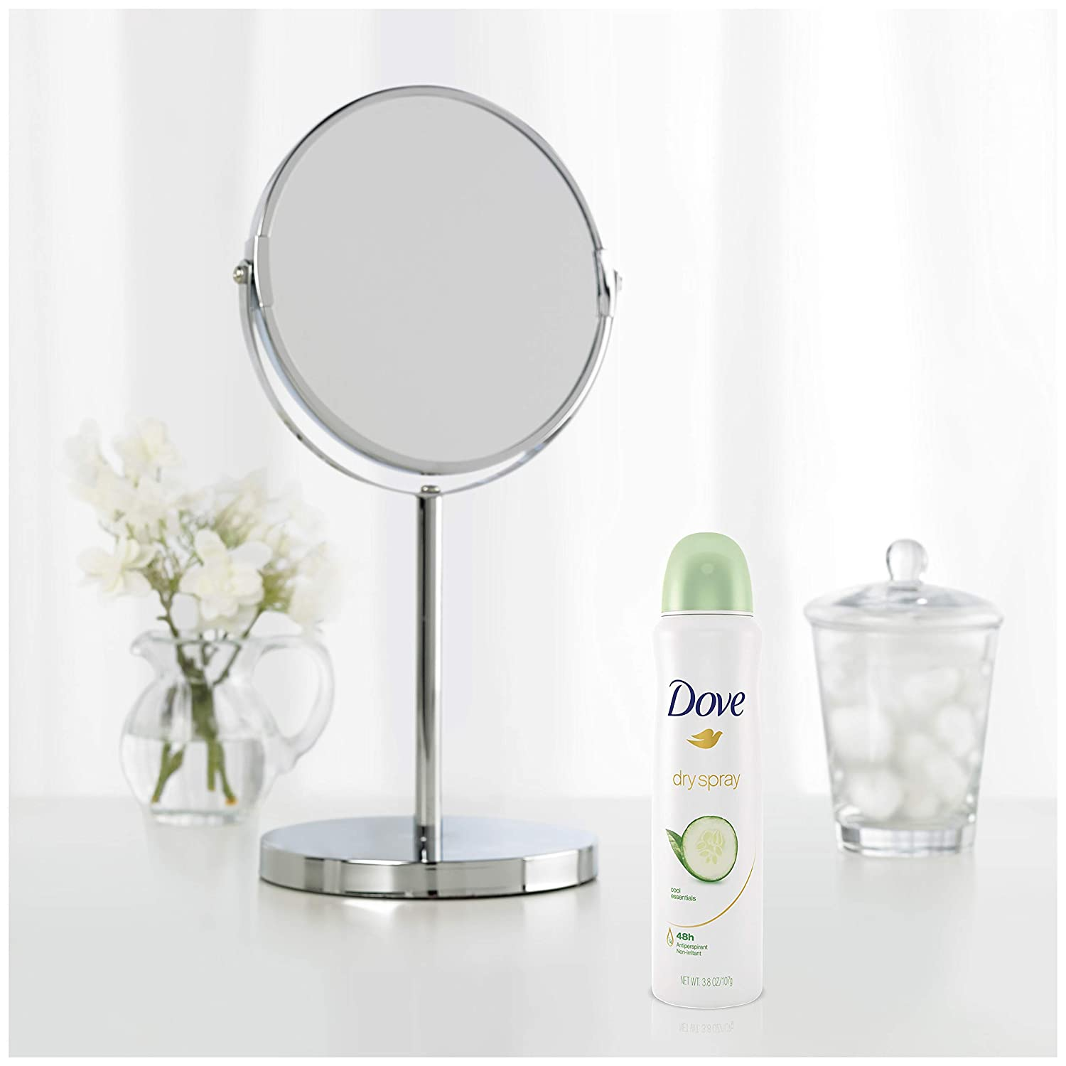 A sample of Dove Women Cool Essentials Dry Spray beside a makeup mirror with flowers in the background.