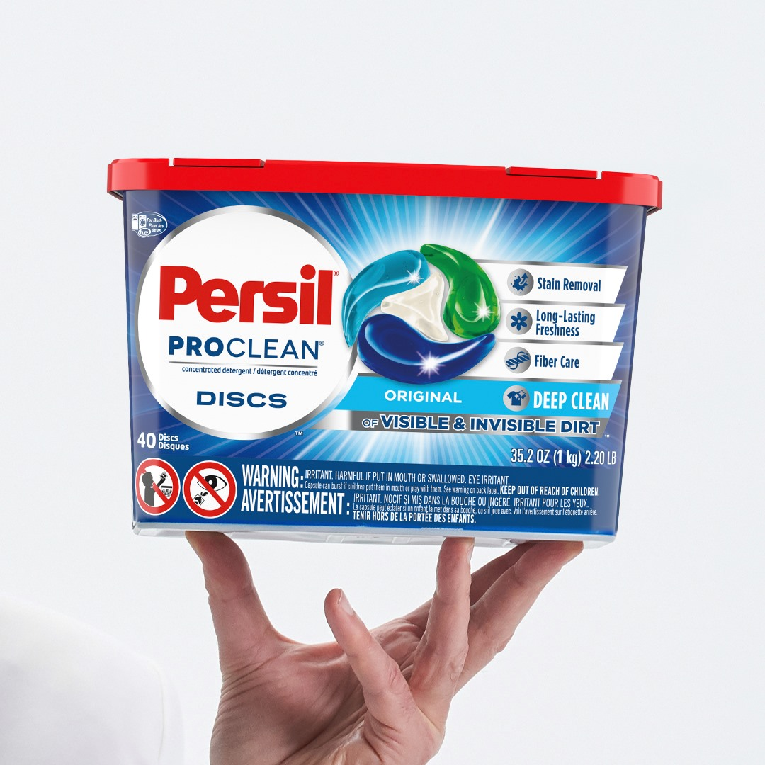 A hand holding up a Persil ProClean® Discs sample.