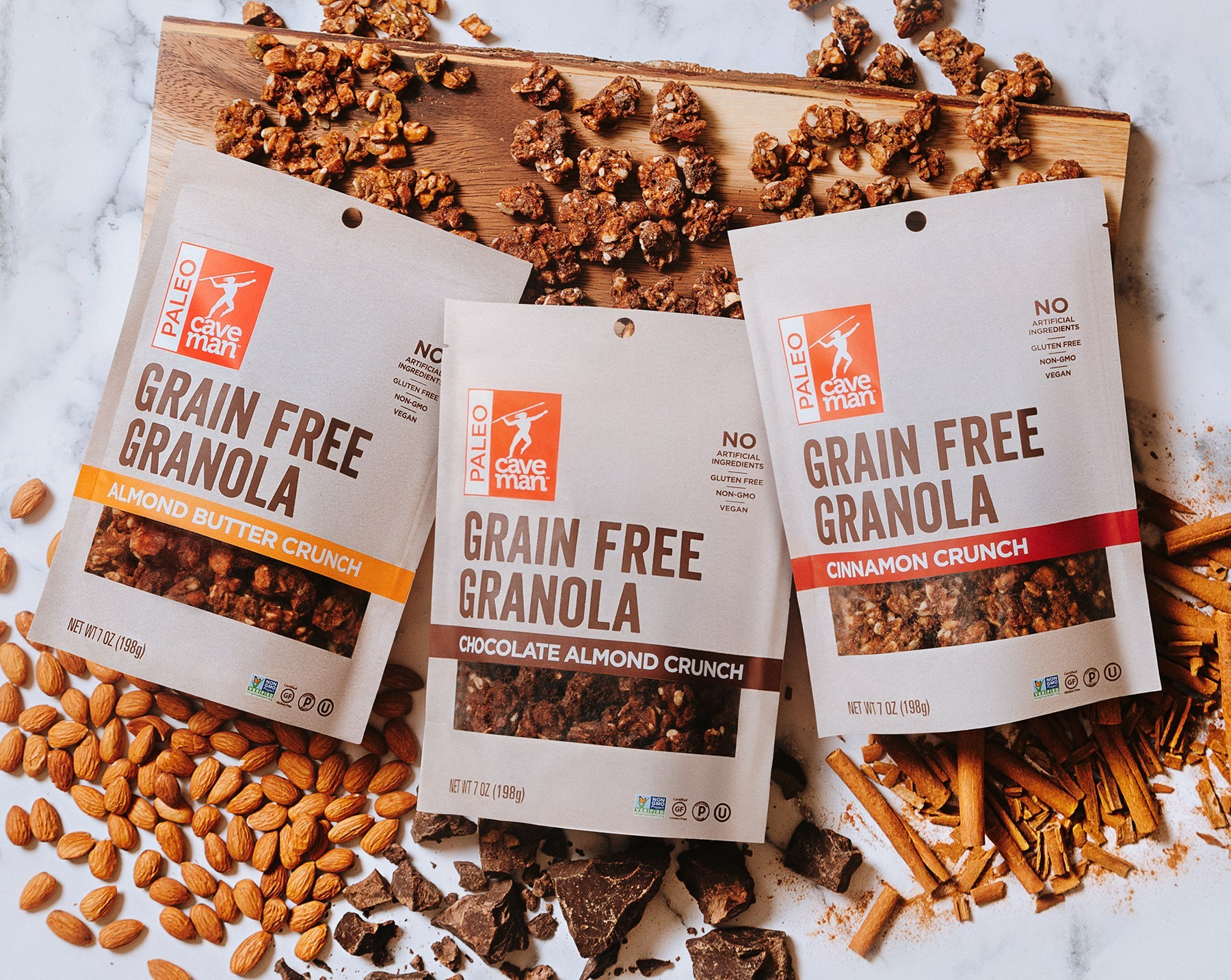 Three samples of Caveman Foods Grain Free Granola surrounded by granola on a cutting board.