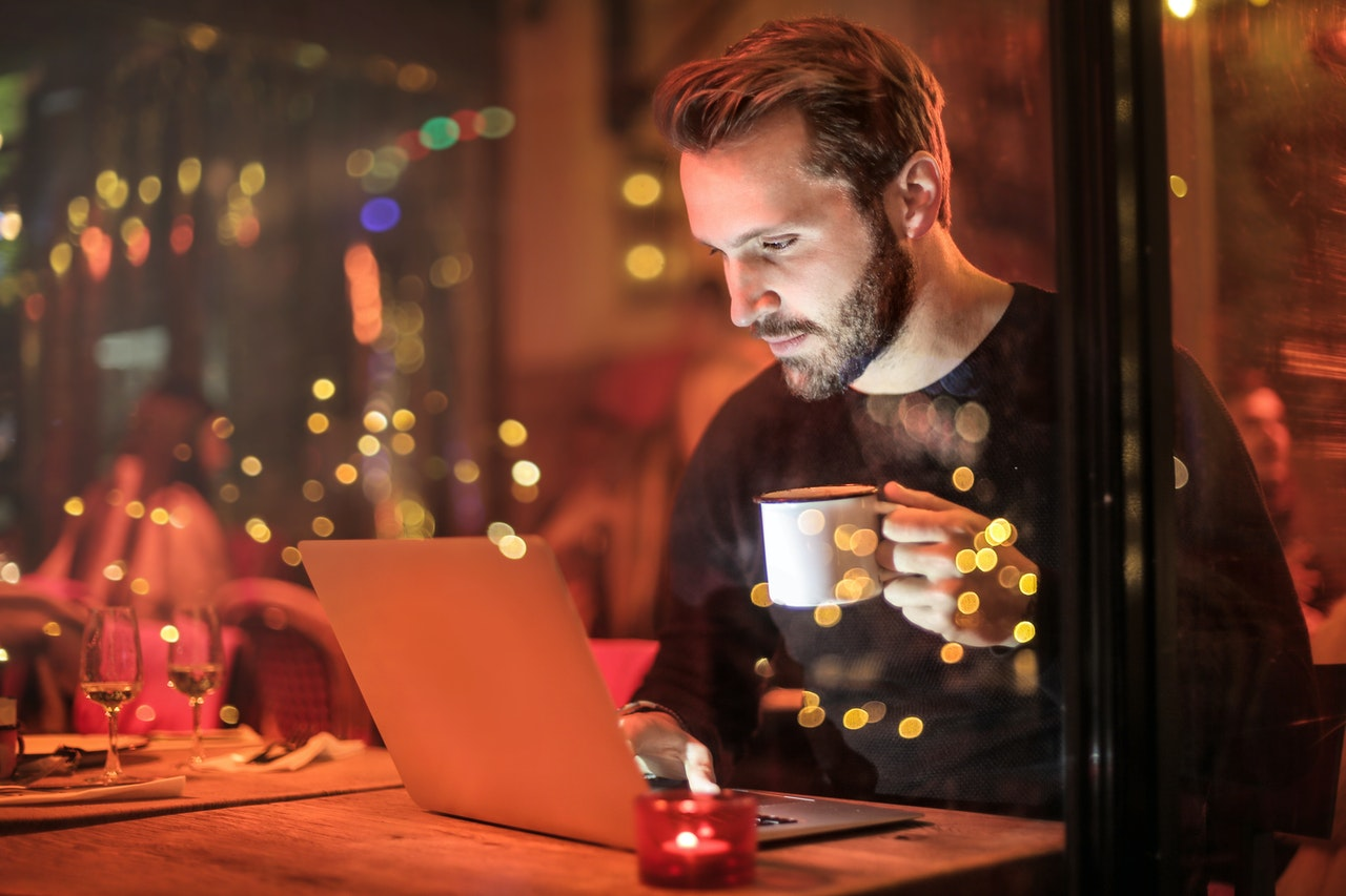 Someone holding a mug while at a restuarant working on a computer.