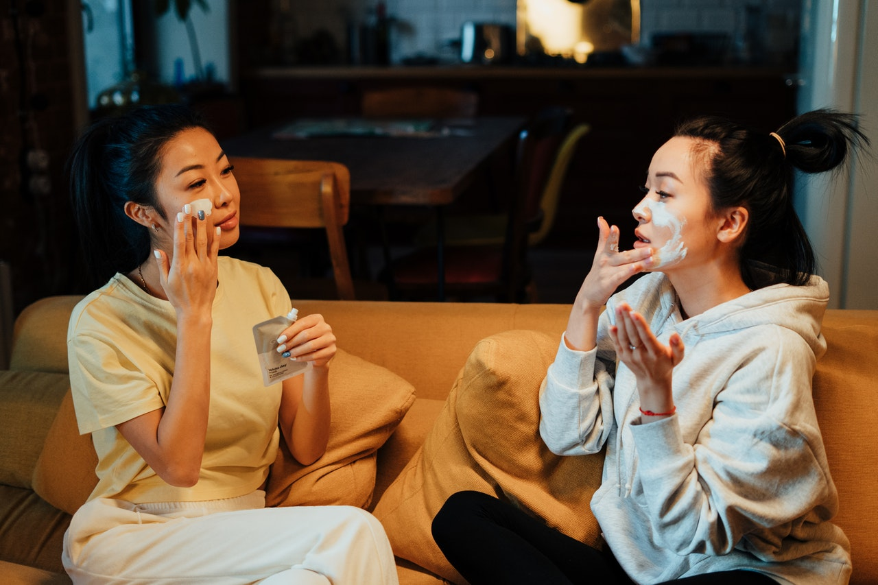 Two people with face masks on sampling DIV beauty products sitting on a couch looking at each other.