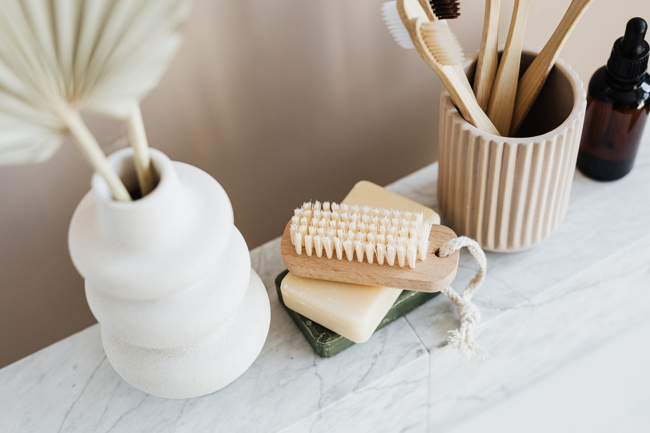 Toothbrushes, soap bars, body scrubs, serum and beauty products all pictured on top of a marble countertop.