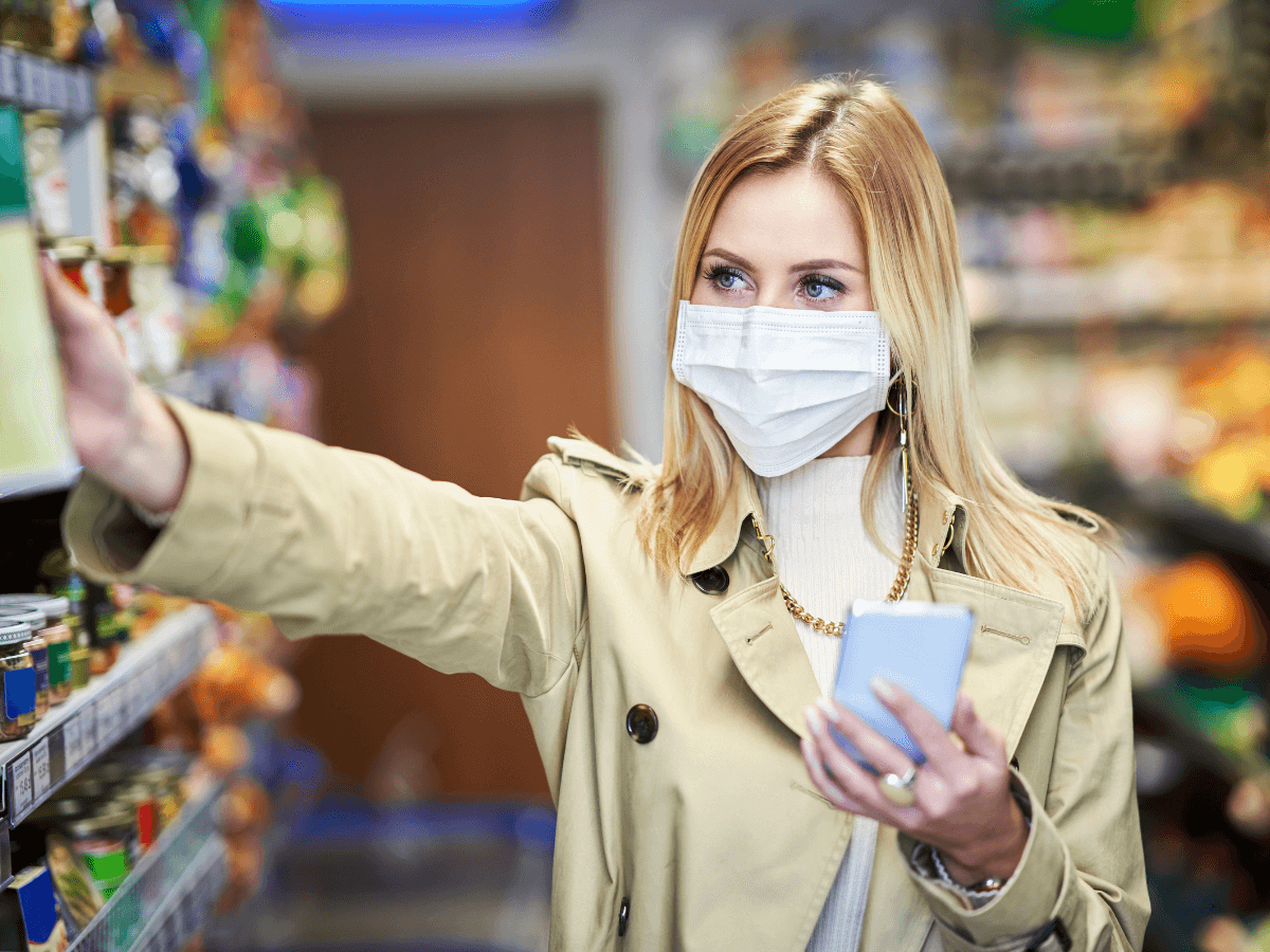 Someone in a store with a mask on shopping, looking at a product in the aisles with one hand and their phone in the other. .
