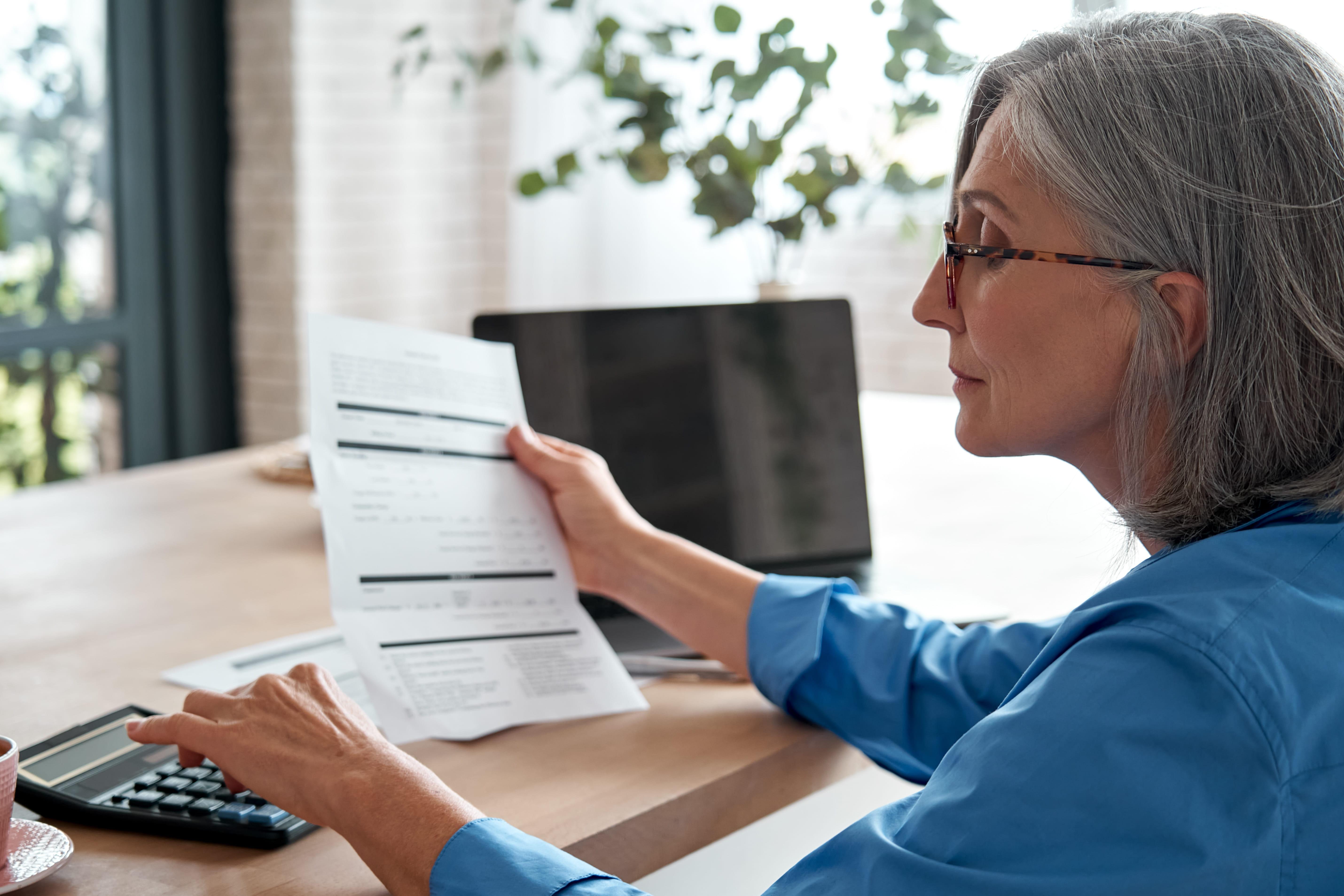 senior mature business woman holding paper bill using calculator