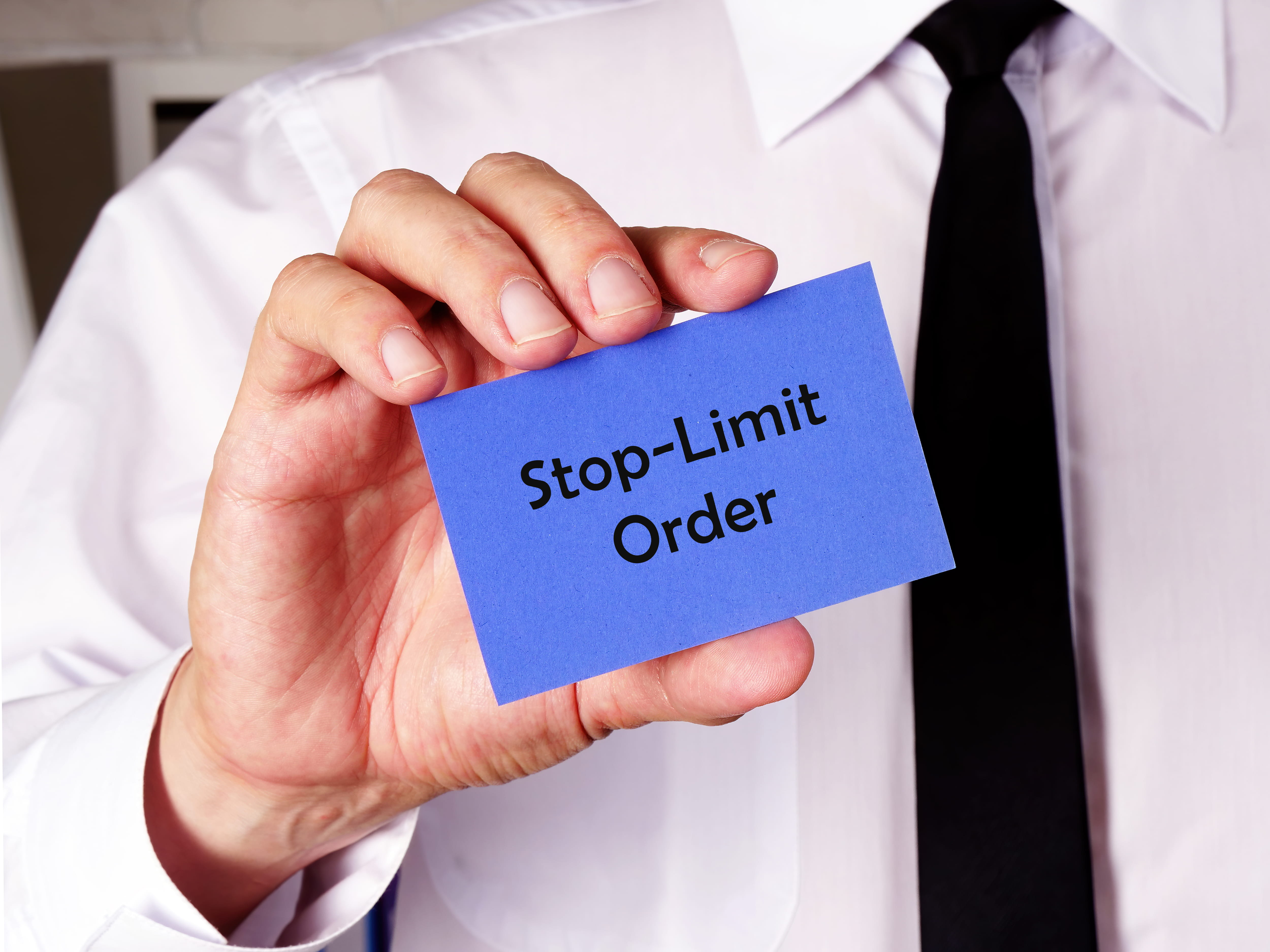 business man holding blue card with stop-limit order written on it