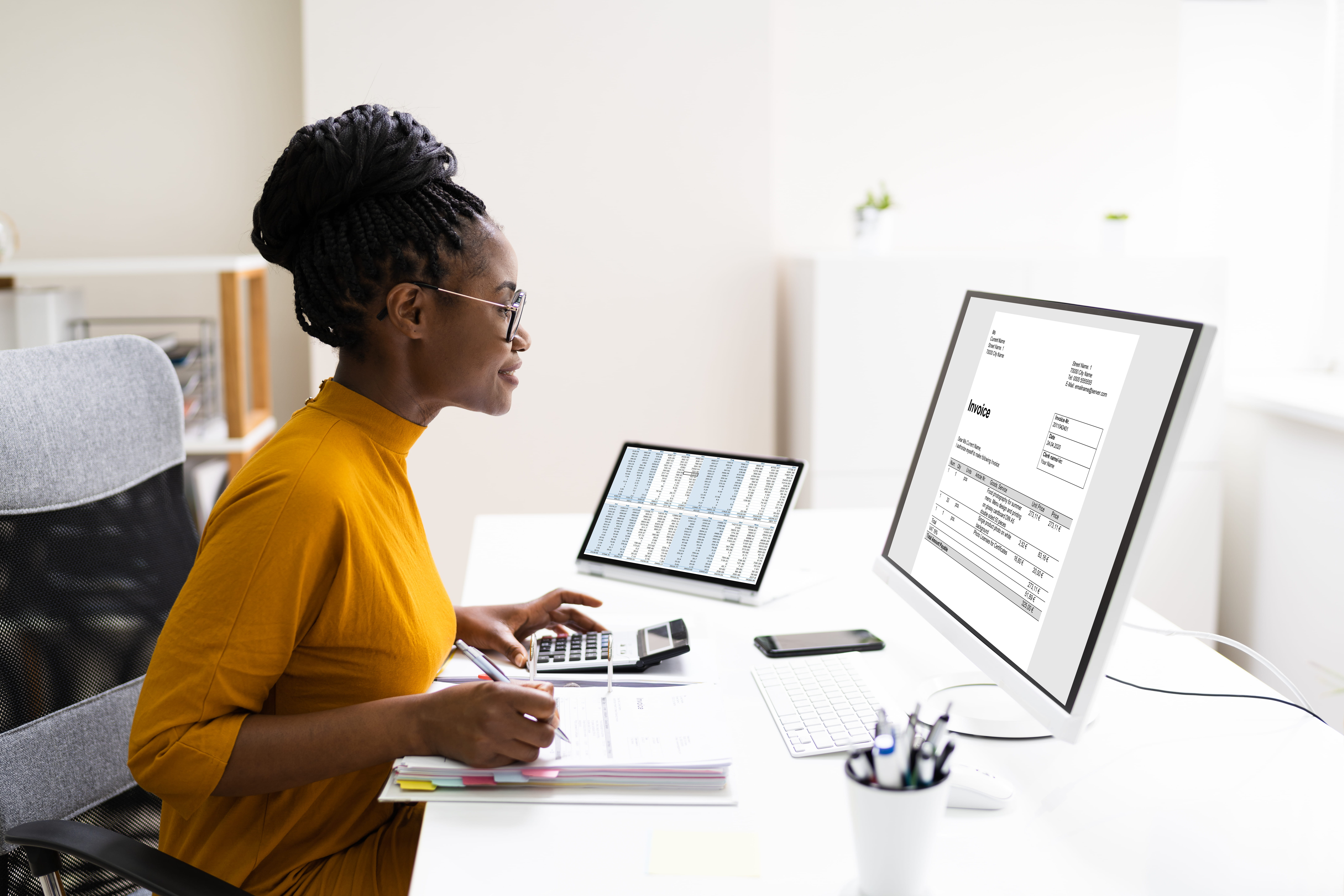 professional female accountant at desk on computer with calculator