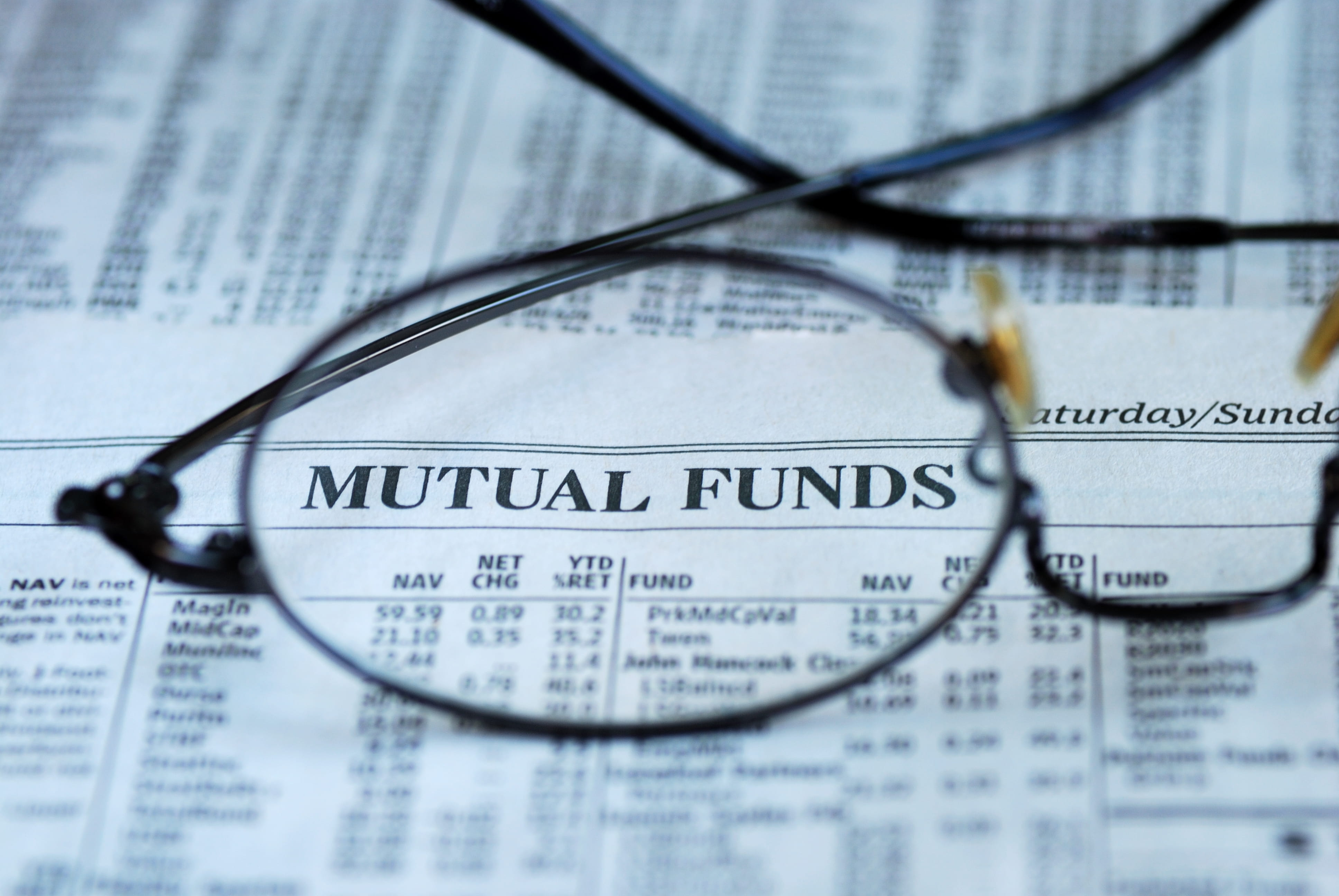 glasses focused on mutual fund page of newspaper