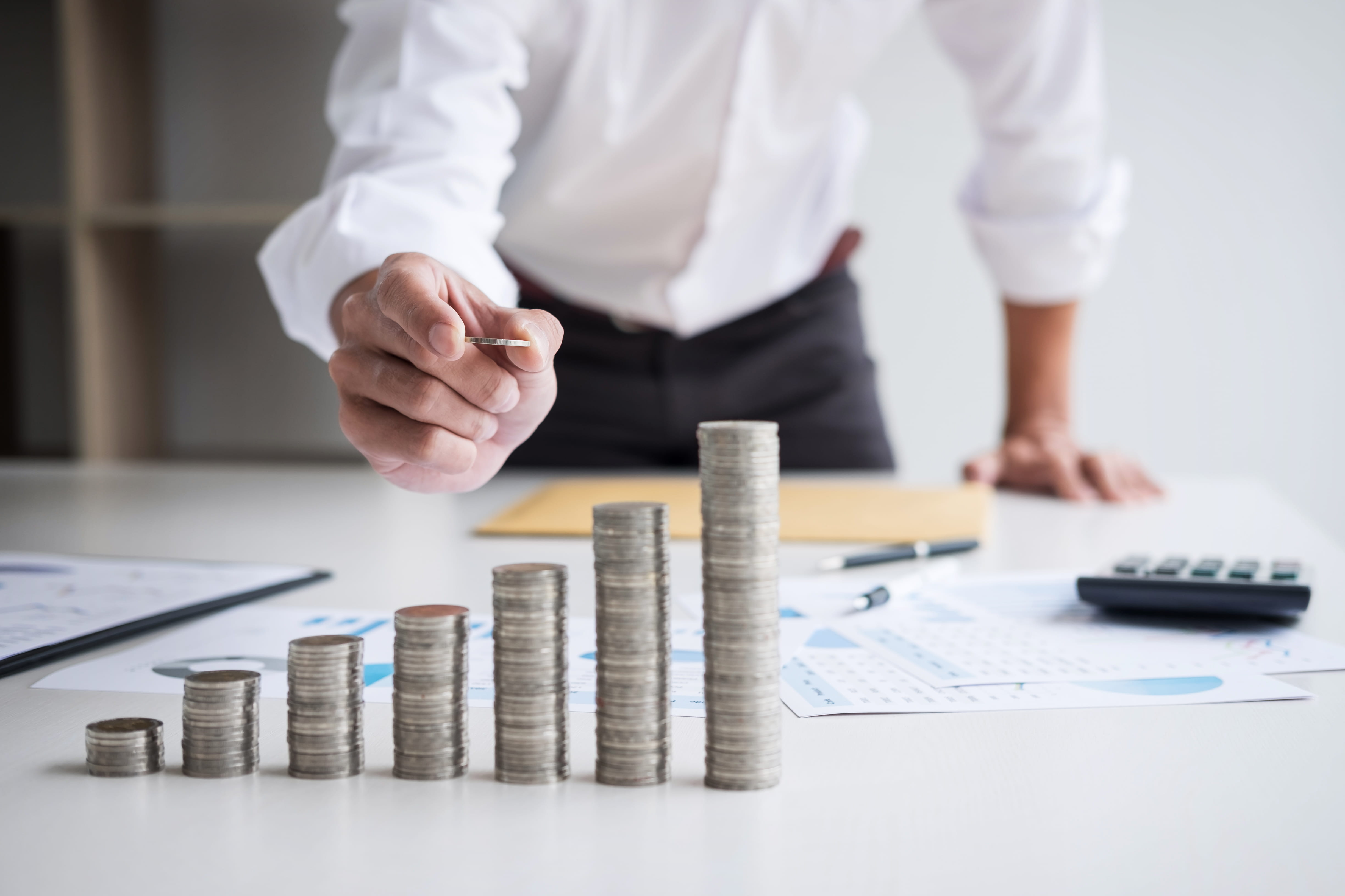 business stacking gold coins on desk
