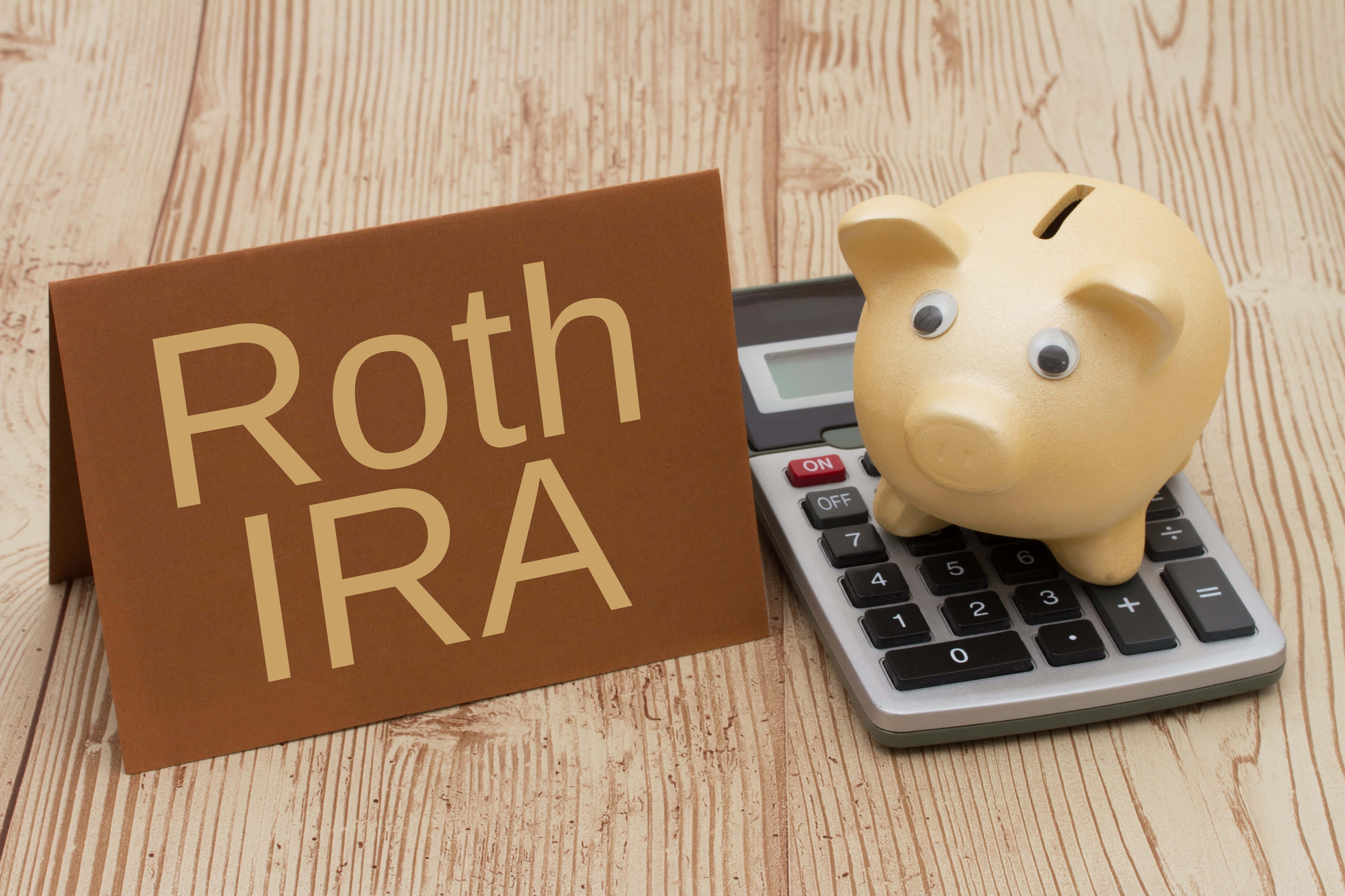 roth IRA plan card next to piggy bank on calculator