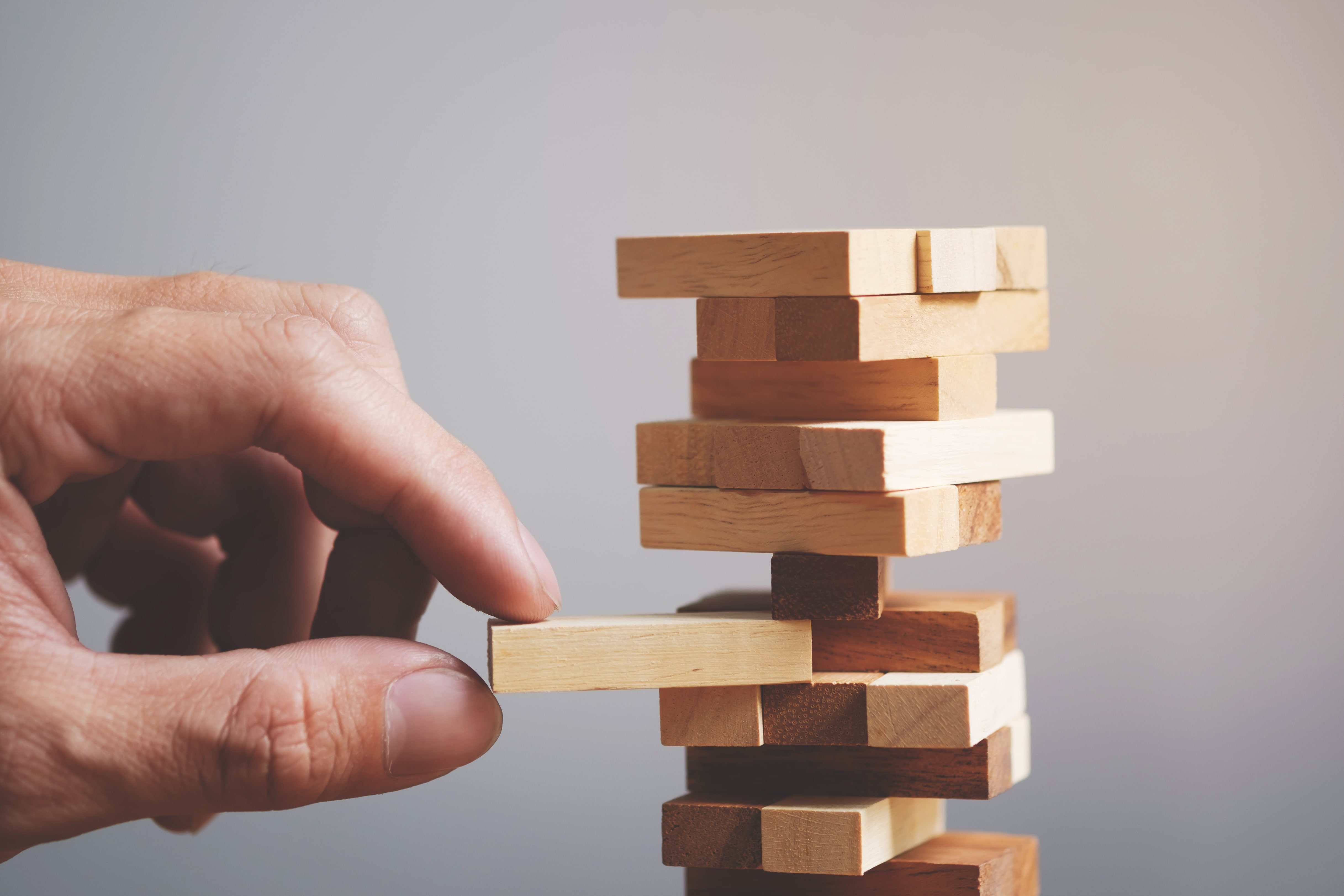 Wood tower representing the risk of investing