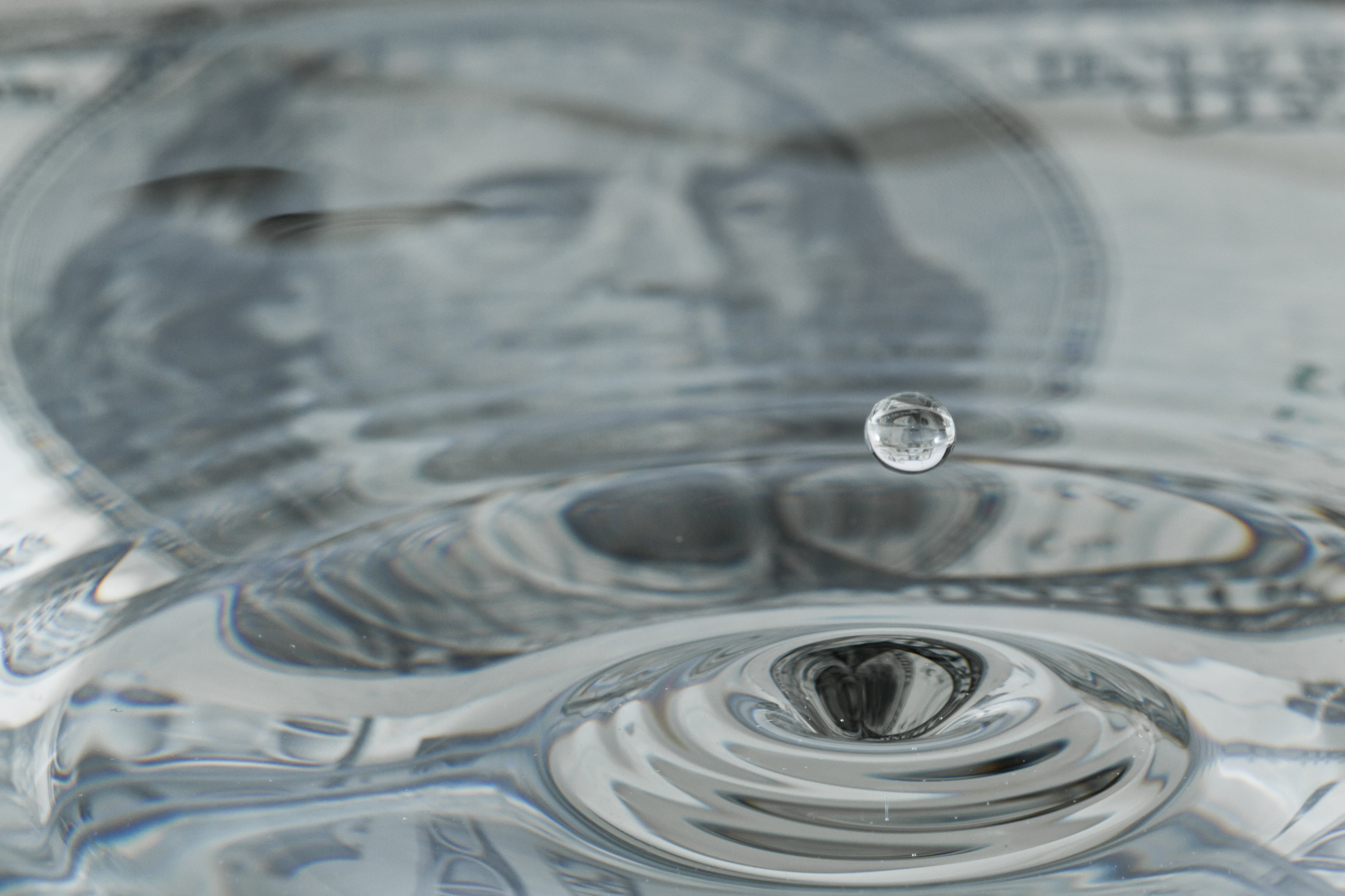 A dollar with water on top to simbolize liquid assets