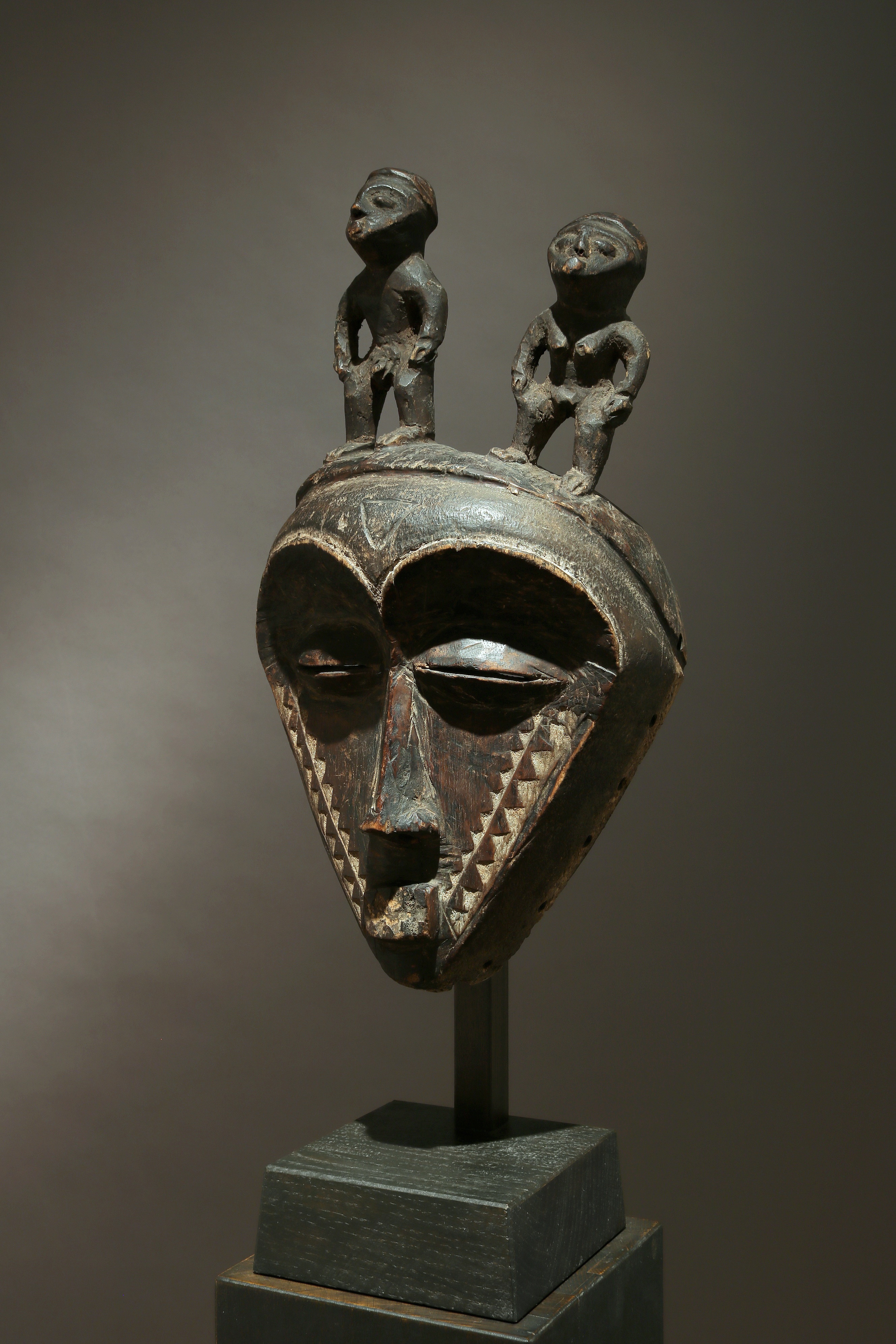 Triangular face mask with figures on top