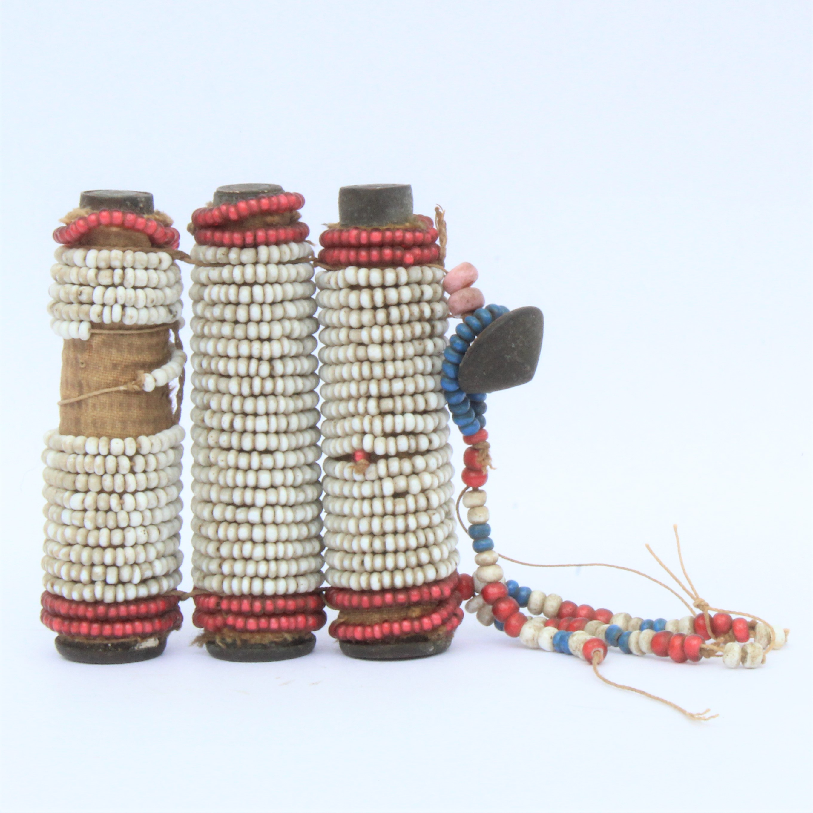 A basketry cup, three beaded Martini Henry rifle cases and two shell bracelets.
