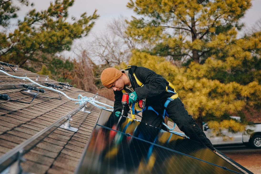 EightTwenty team member installing panels on a rooftop