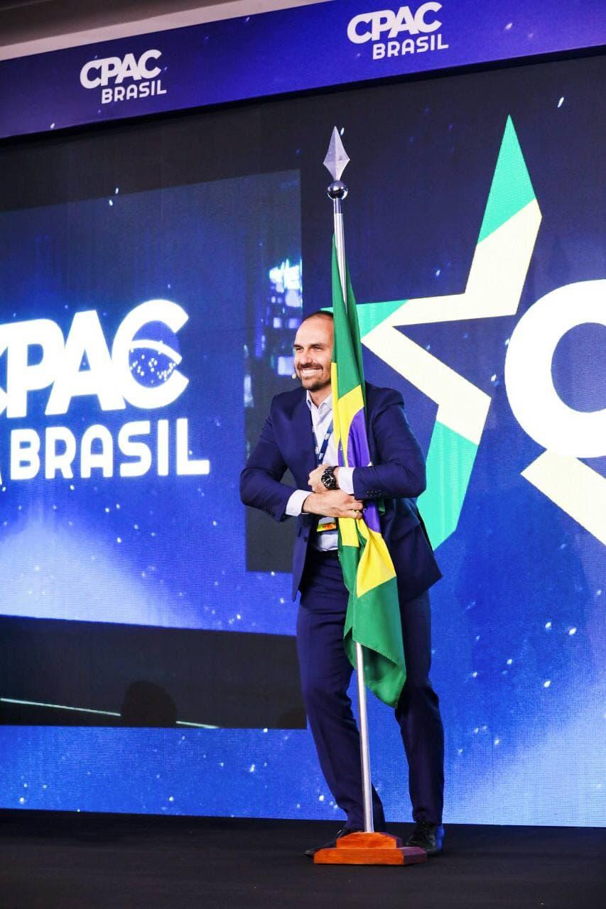 Eduardo Bolsonaro abraçando a bandeira do Brasil no CPAC 2019
