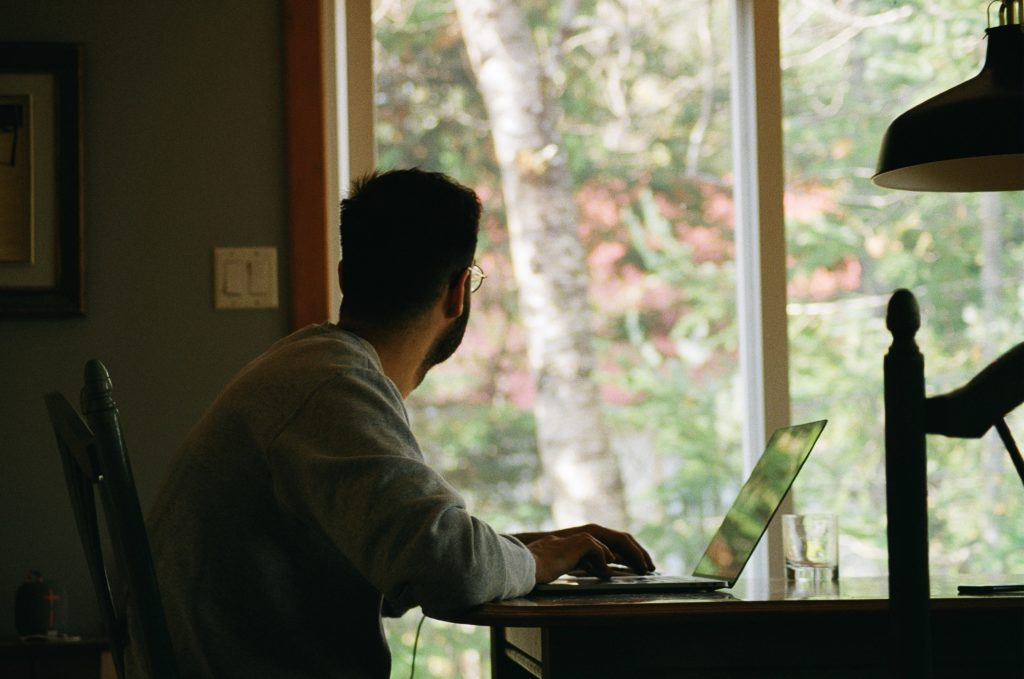 Men looking to an open window while he workes remotely
