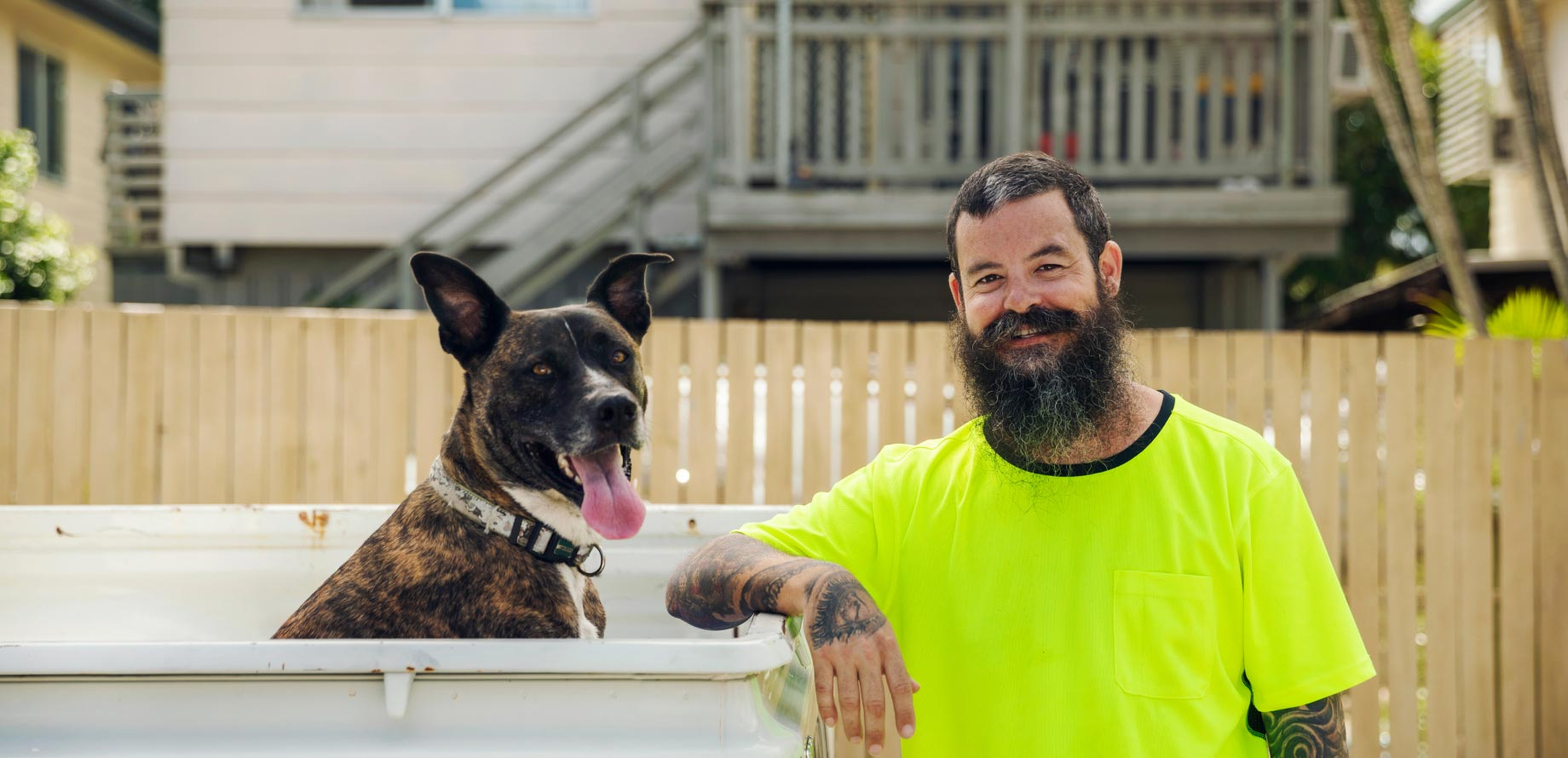 A male tradesperson standing next to his dog thats sitting in his ute