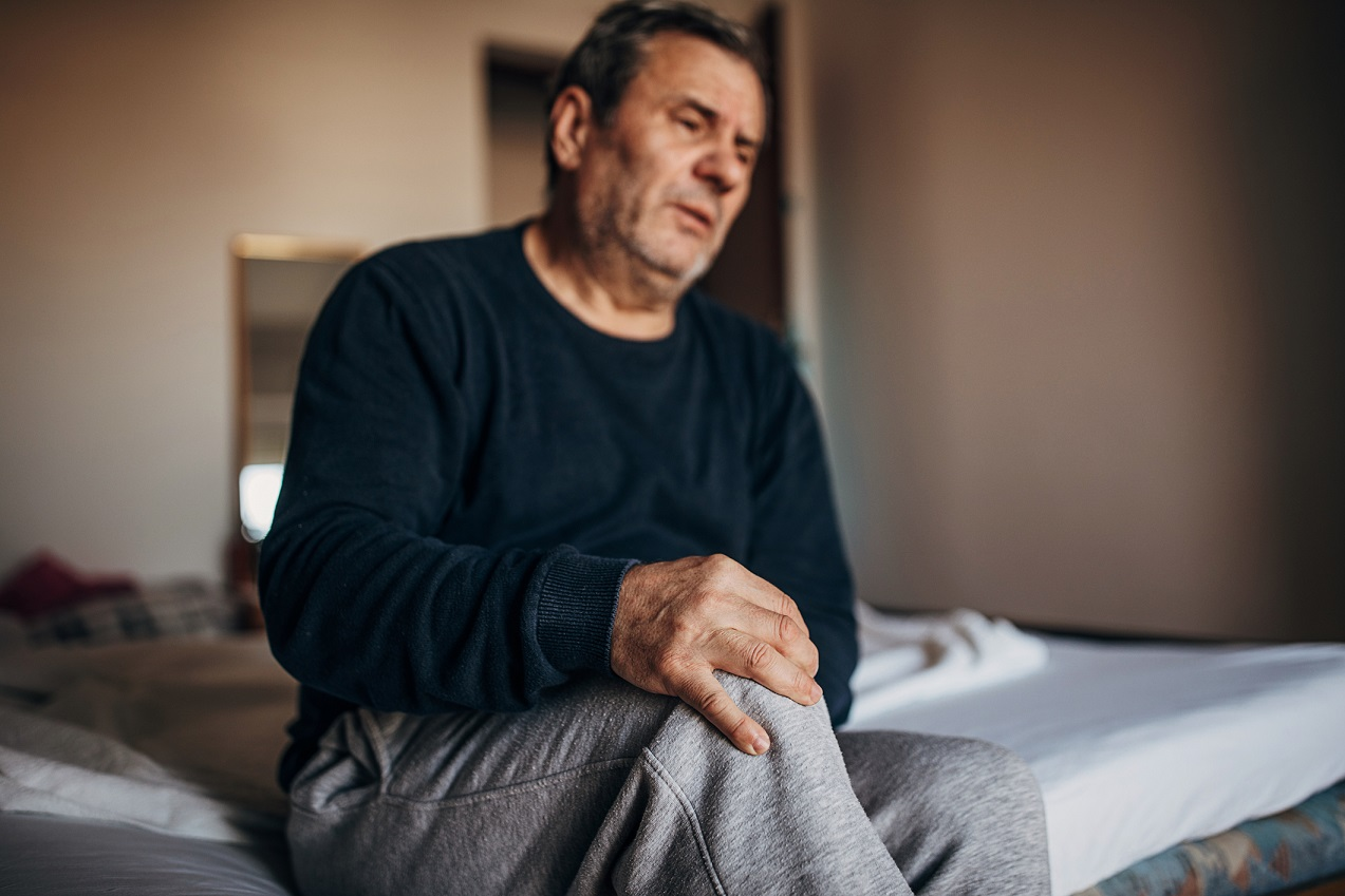 Older man holding knee in pain