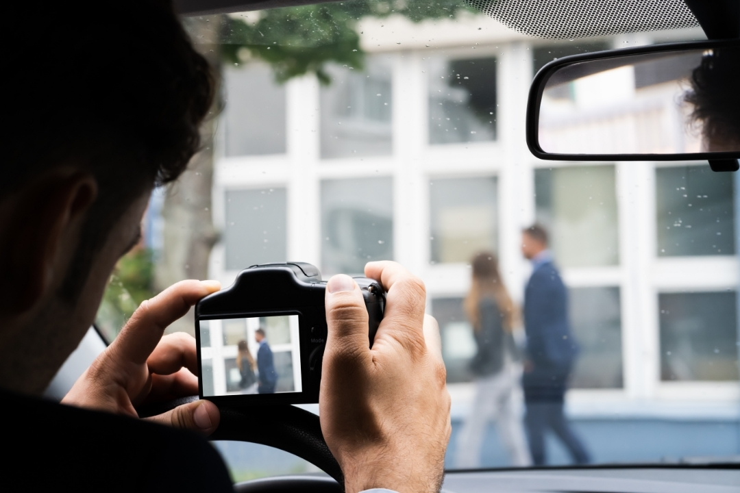 Person taking photo of people from car