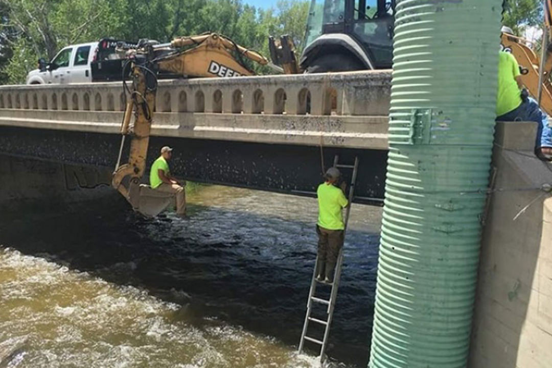 Two men dangerously working by river