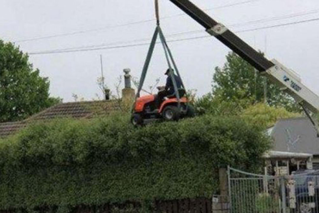 Man in lawnmower hanging from crane