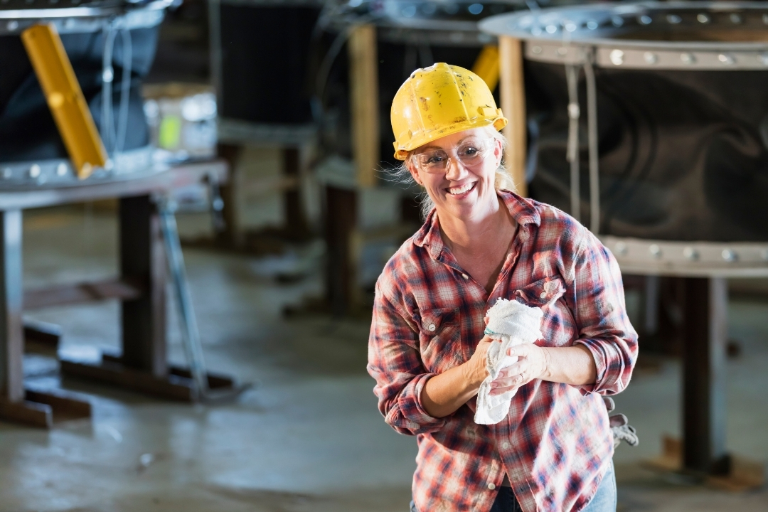 Lady with a hard hat wiping oil off hands