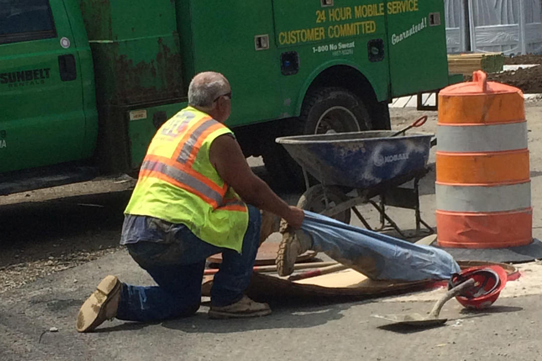 Man holding other man working inside sewer hole