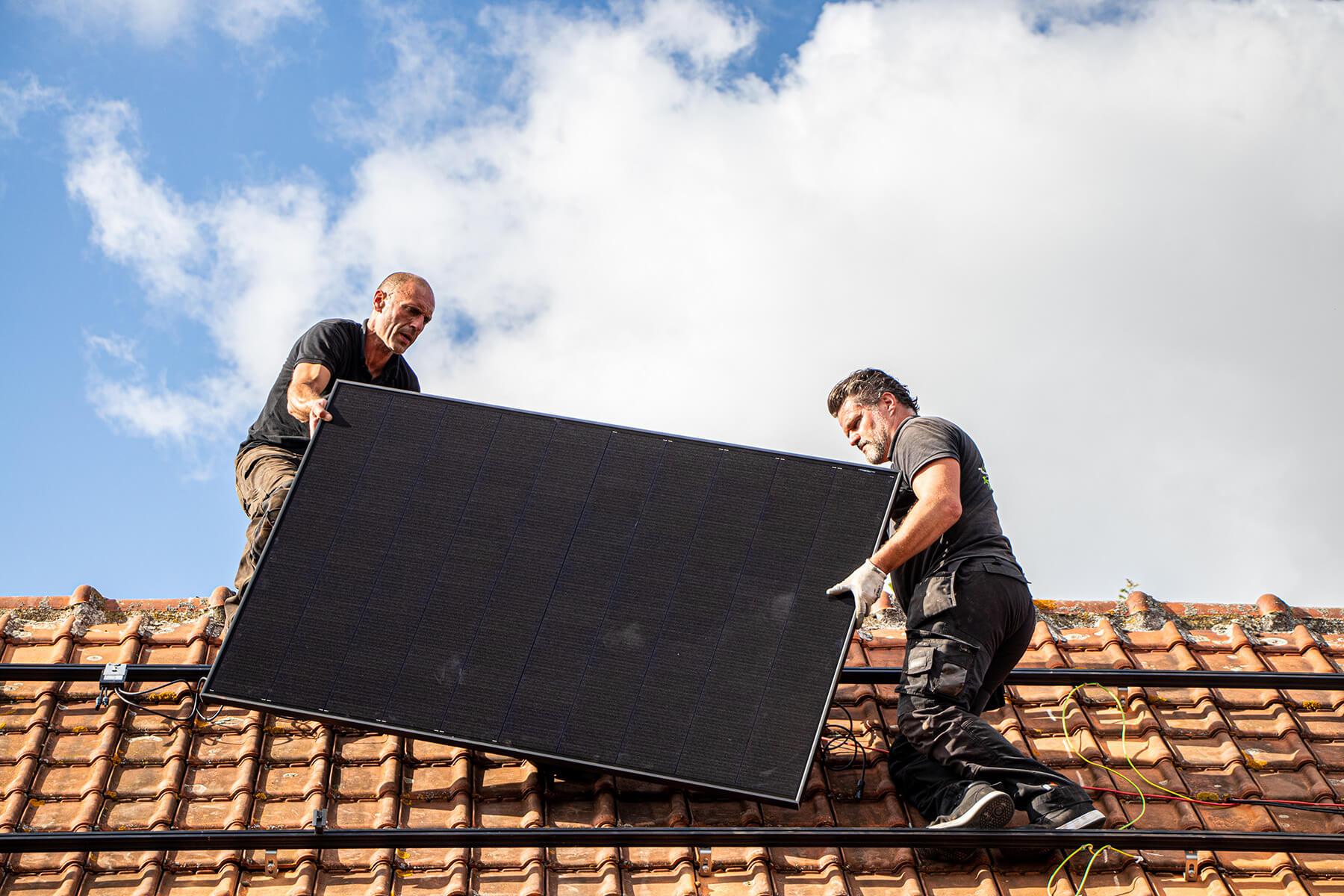 2 zonnepanelen installateurs dragen een paneel op een dak