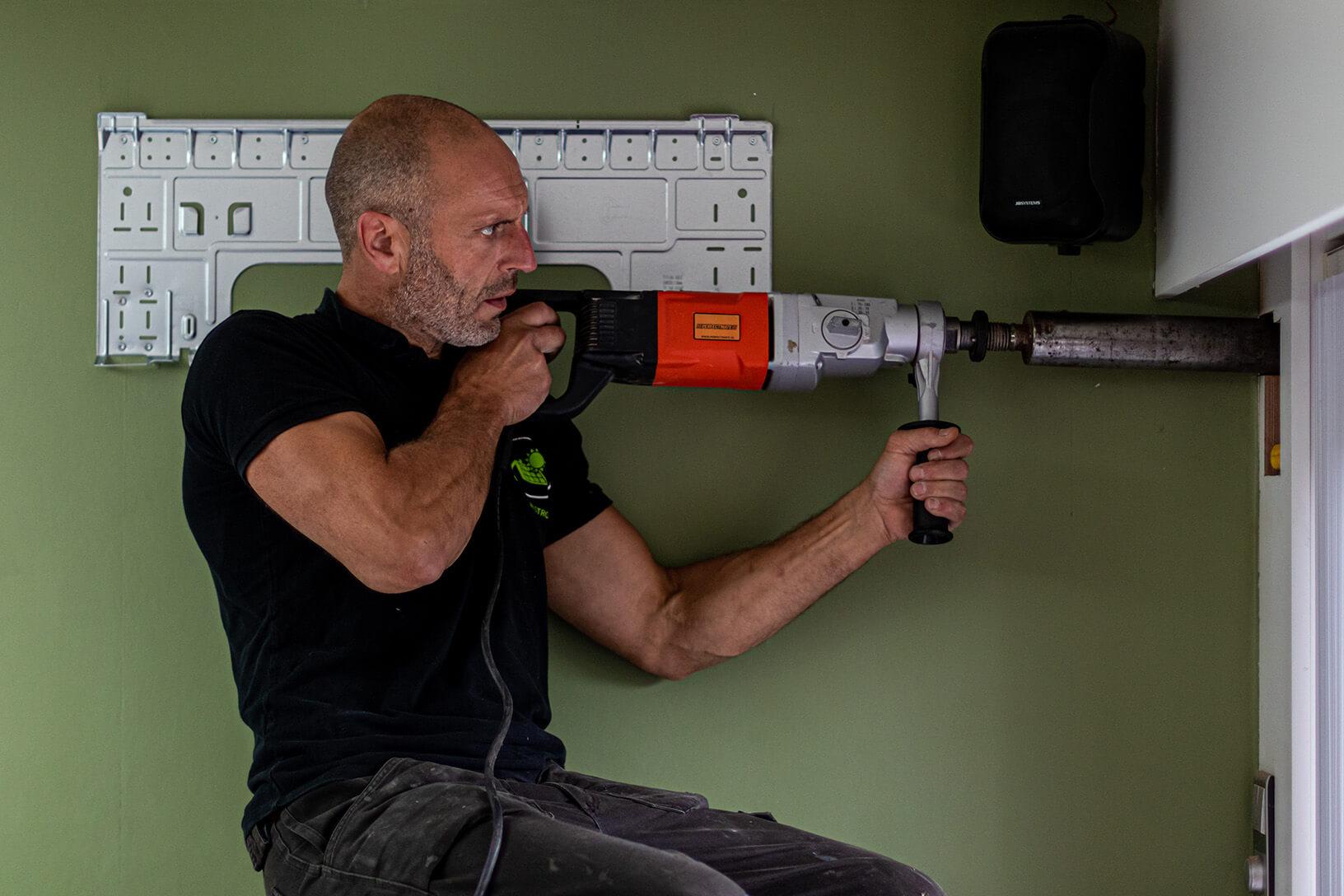 Airco installateur boort gaten in de muur.