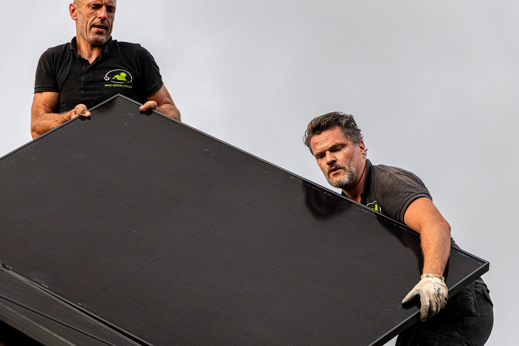 Twee zonnepanelen installateurs dragen één zonnepaneel naar boven op een dak in het waasland.