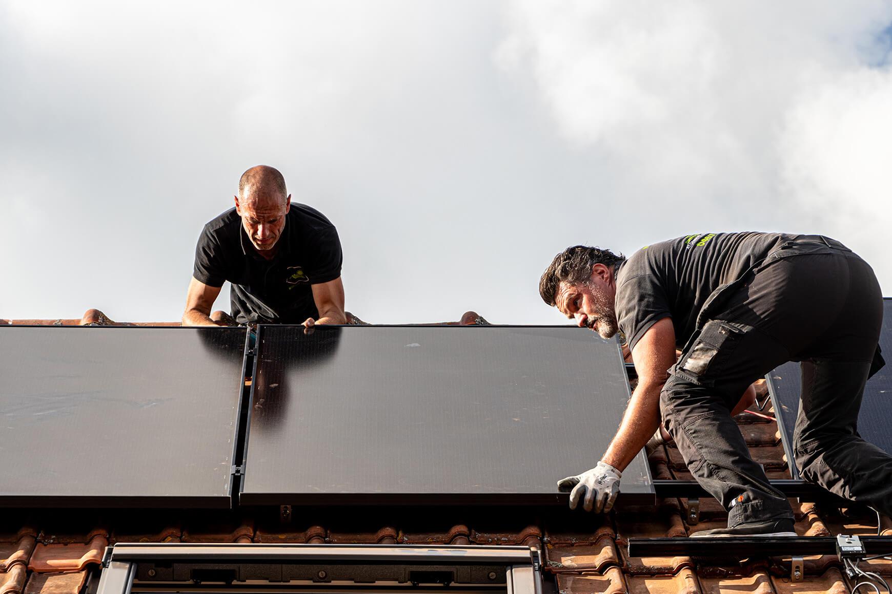 Twee zonnepanelen installateurs positioneren enkele panelen op een dak.