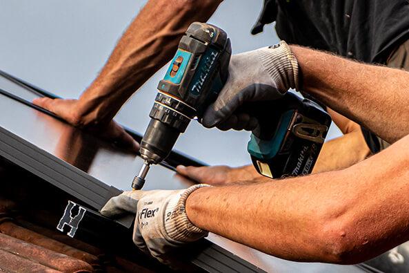 Close-up van een interactie met een boormachine op een dak in het waasland.