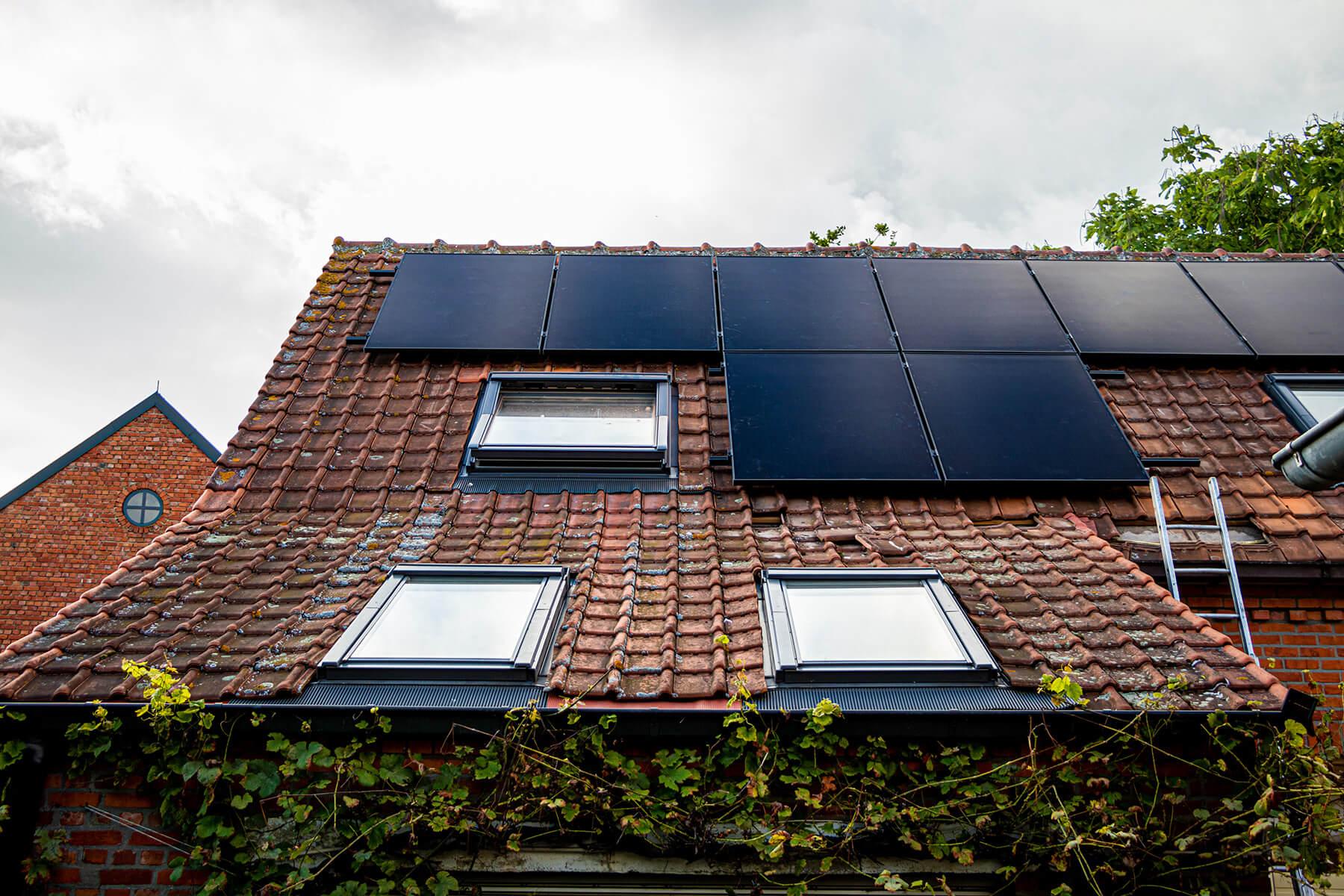 Een overzicht van een schuin dak waarvan de bovenste helft vol ligt met zonnepanelen.