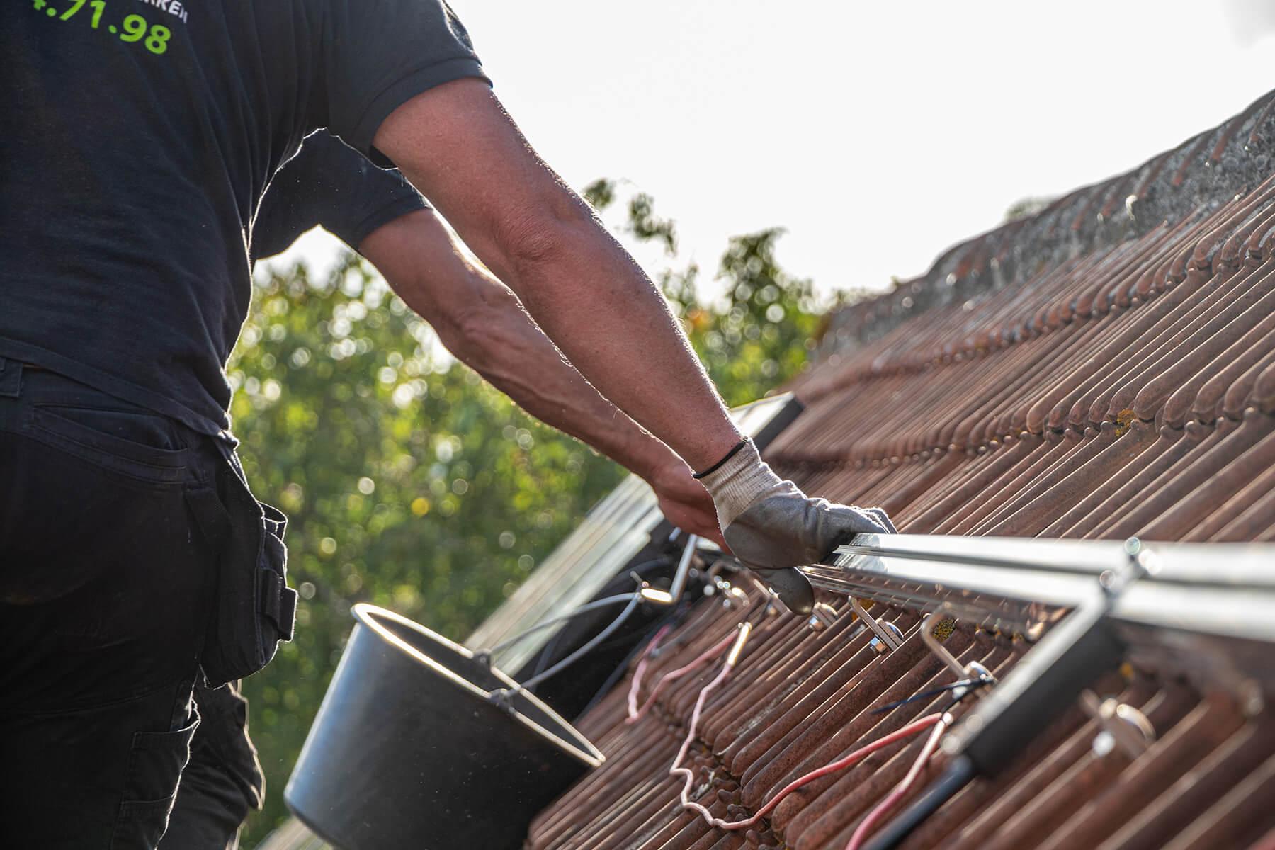 Twee zonnepanelen installateurs grijpen naar een rail op het dak.