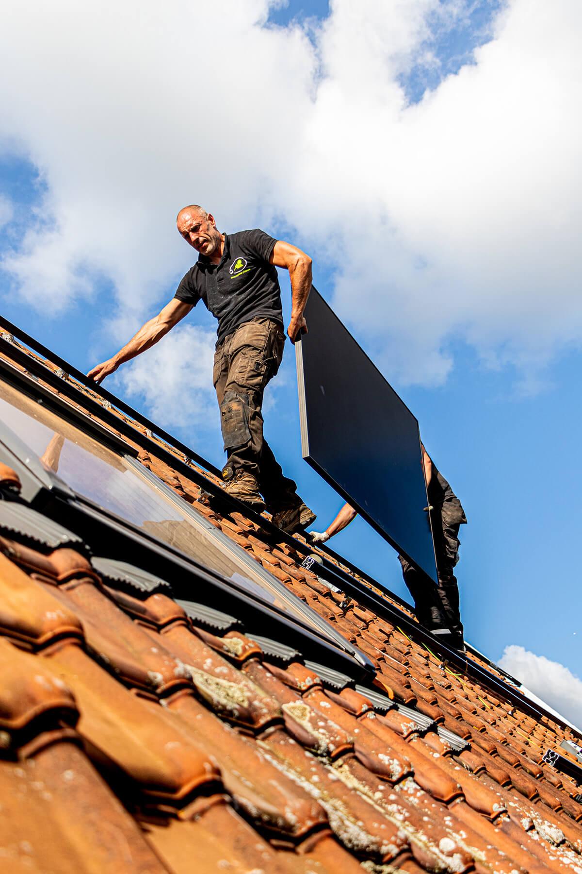 Twee zonnepanelen installateurs dragen een paneel over het dak.  Een helderblauwe hemel in het waasland.
