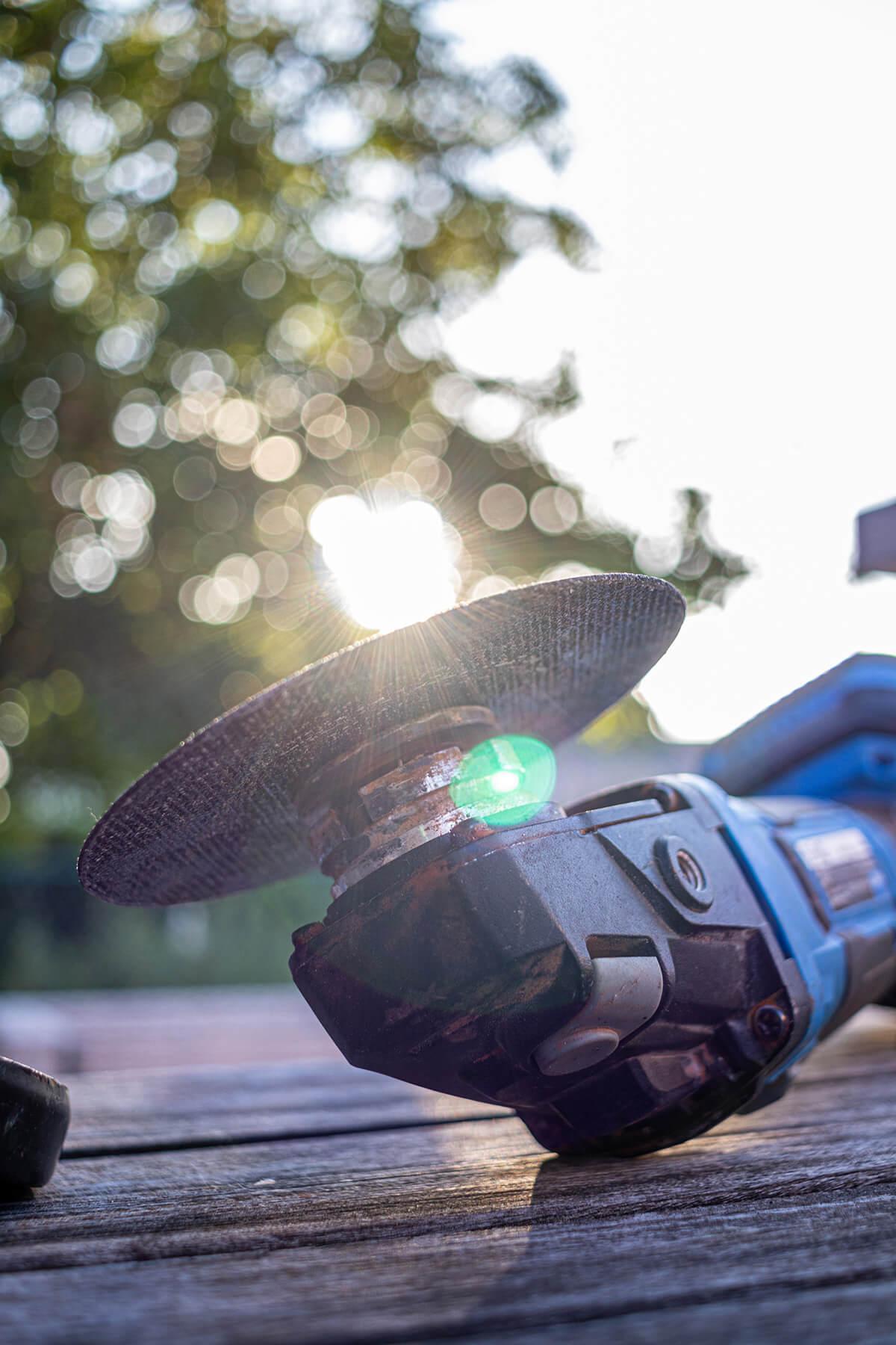 Close-up van een slijpschijf in zonlicht tegen vervaagde achtergrond.