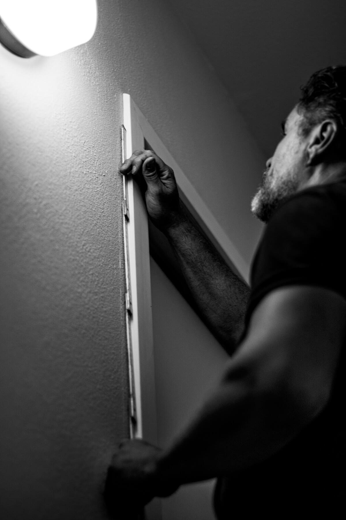 Airco installateur meet deurlijst in zwart wit.