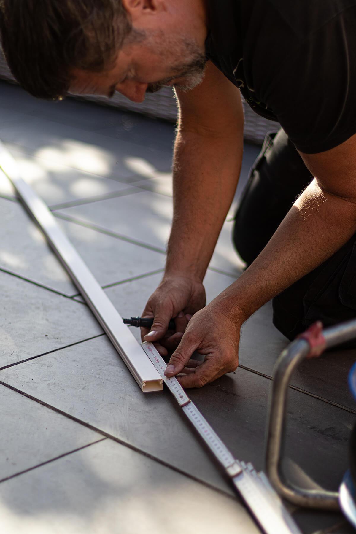 Airco installateur meet witte profielen op de grond.