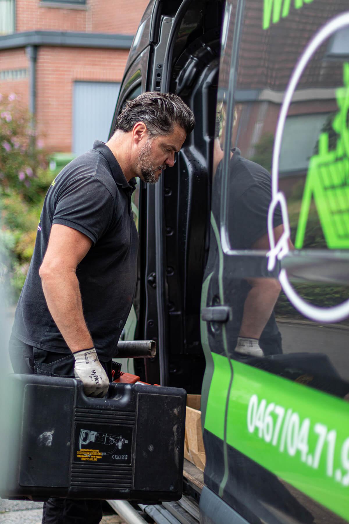 Zaakvoerder zet gereedschapskoffer in camionette.