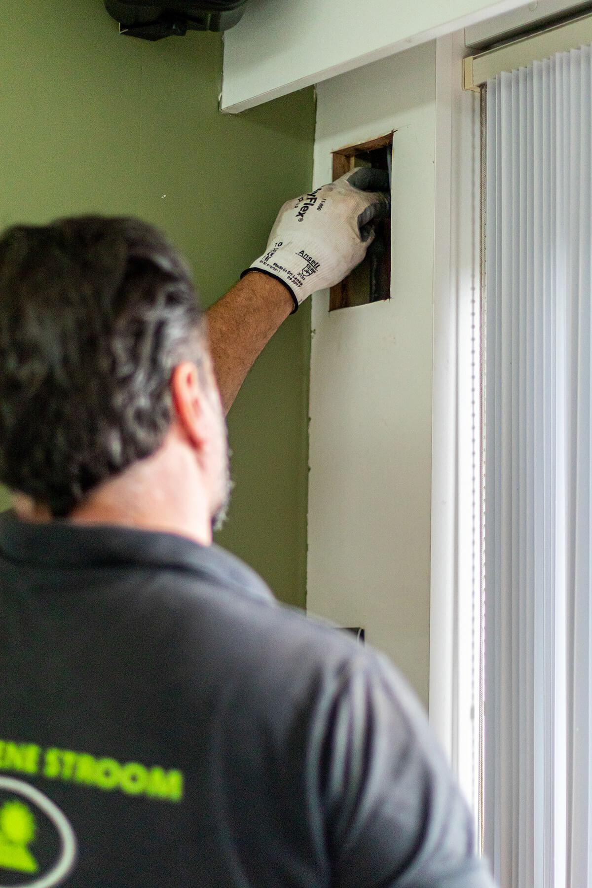 Thuisbatterij installateur voorziet gat voor bekabeling.