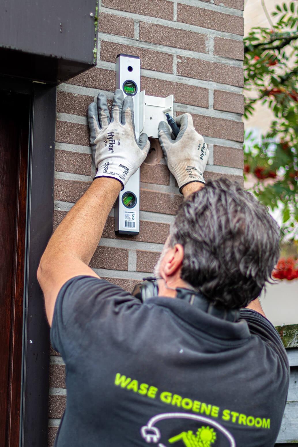 Thuisbatterij installateur zorgt voor een waterpas afwerking tegen de gevel.