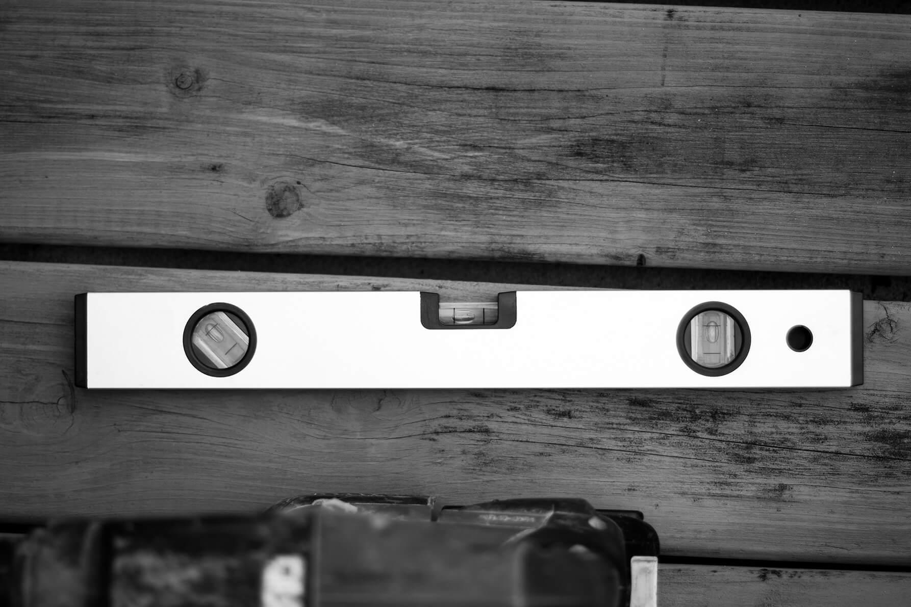Detailfoto van een waterpas op een houten tafel in het zwart wit.