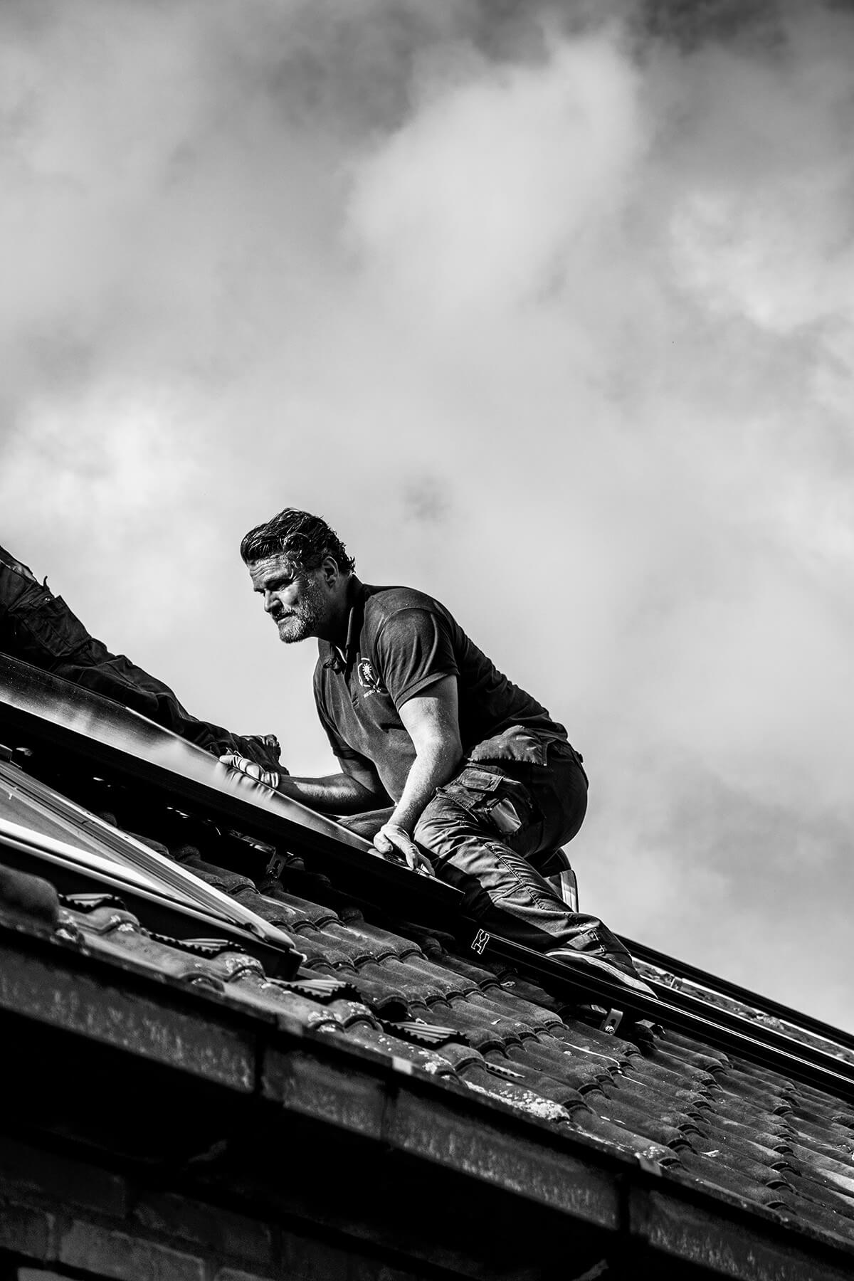 Zonnepanelen installateur houdt zonnepaneel op zijn plaats op een steil dak in zwart wit.