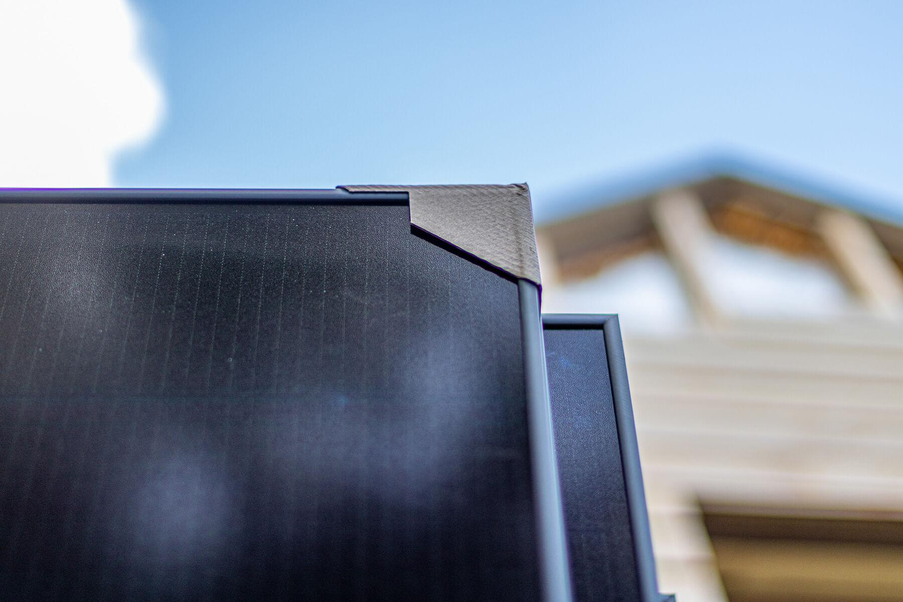 Close-up van de hoek van een zonnepaneel met beschermingskarton tegen een helderblauwe hemel.