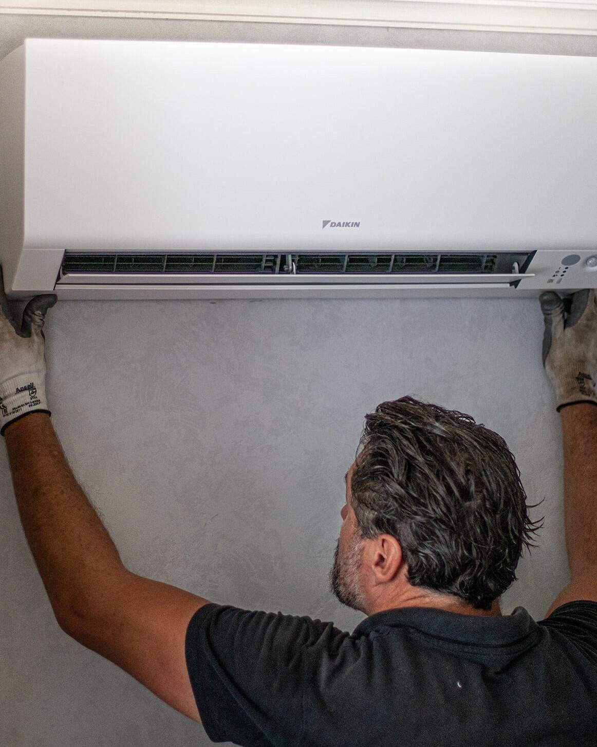 Airco installateur houdt airco unit omhoog tegen de muur om correct te positioneren.