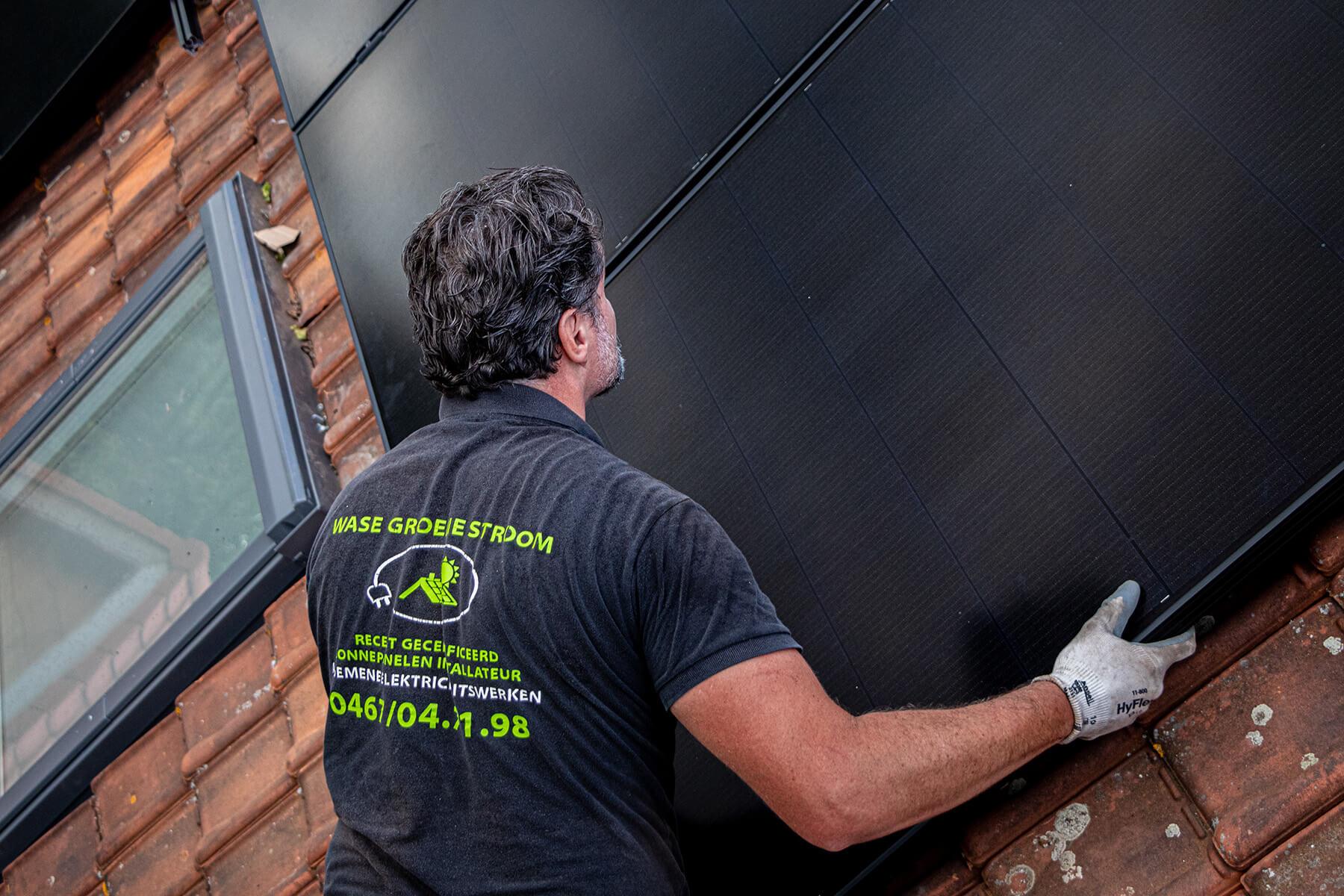 Zonnepaneel installateur lijnt een paneel met precisie af op het dak.